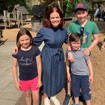 3 children standing smiling with Lindsey a Blue Peter Presenter