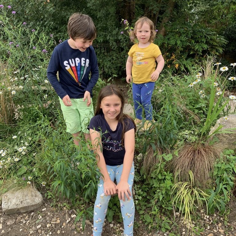 3 children happily posing for a picture on a garden rockery