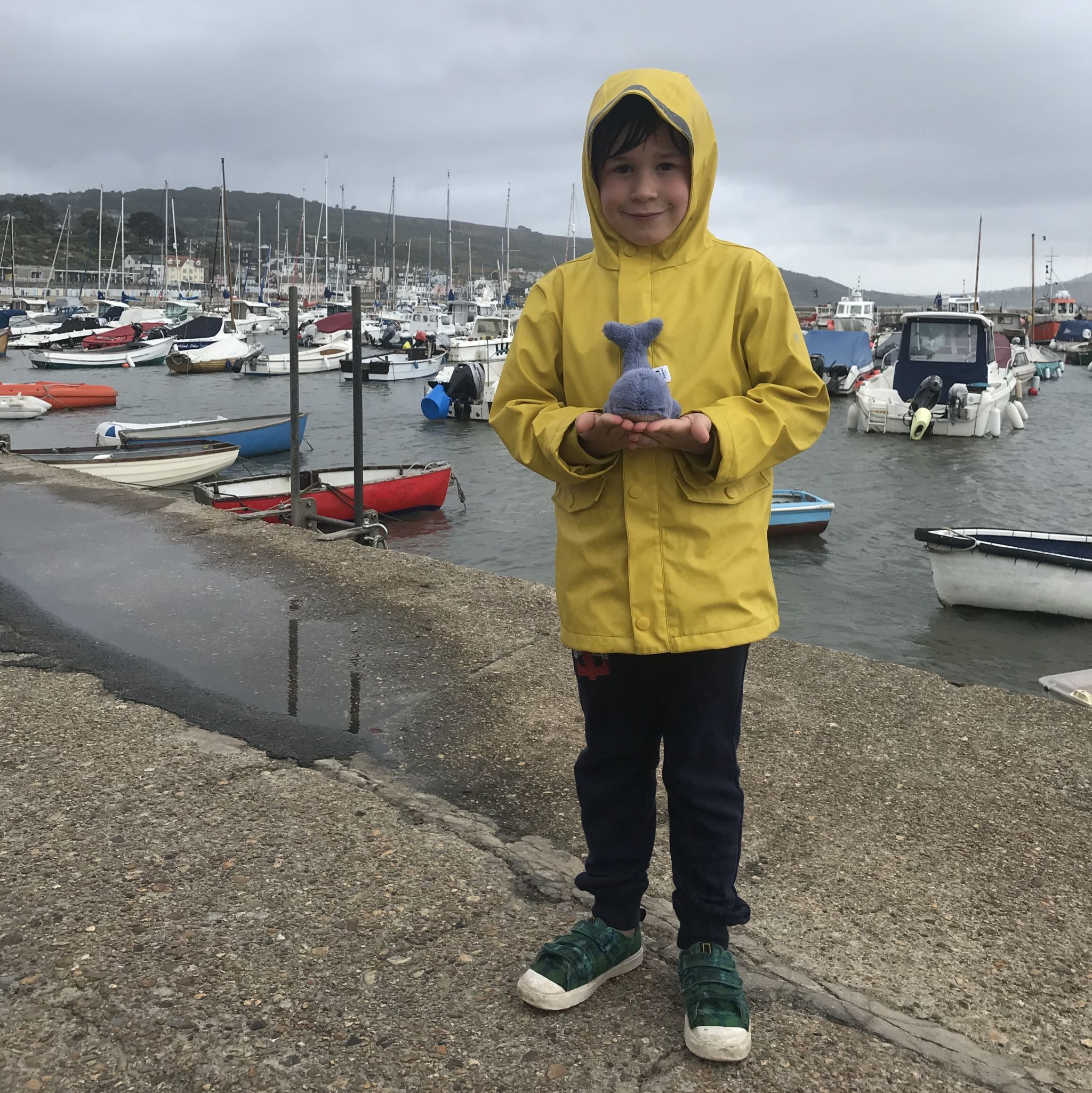 A boy in a yellow fishermans coat holding a toy whale by the harbour