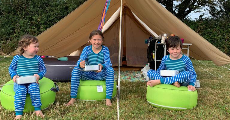 3 children sat outside a tent eating