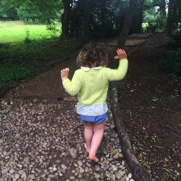 Child walking barefoot through a park