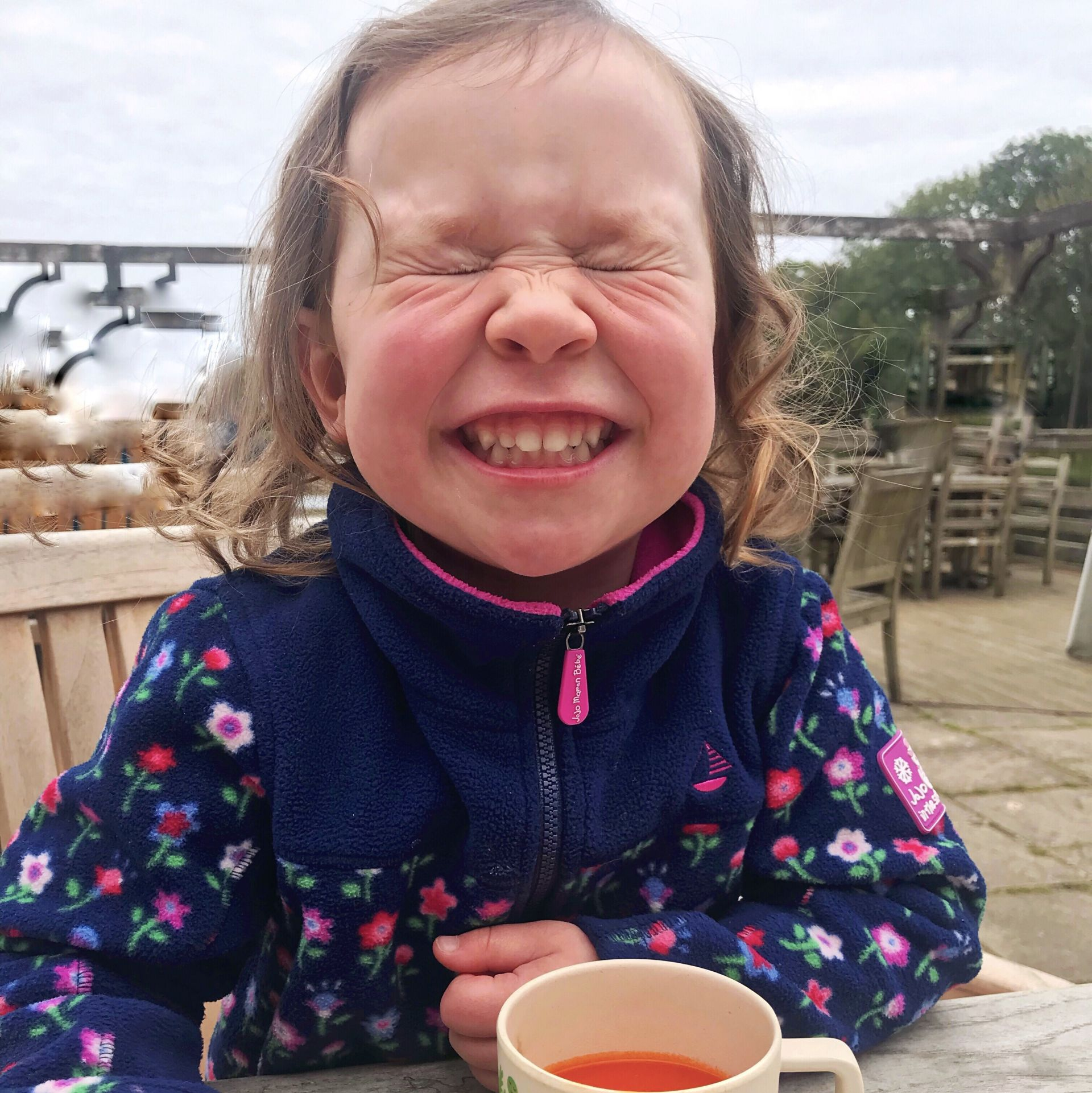A toddler grinning whilst eating soup