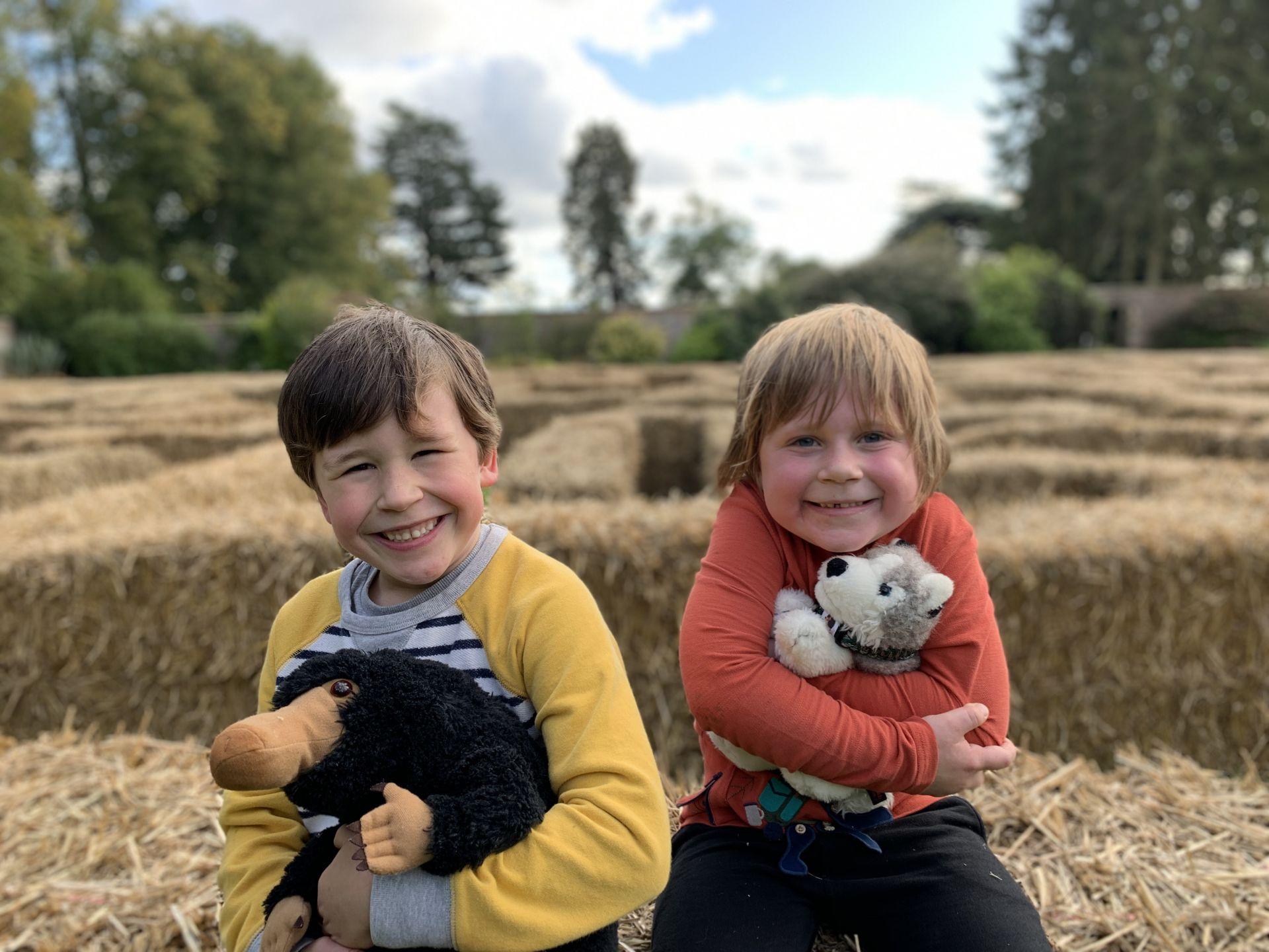 two boys cuddling teddy's on hay bales