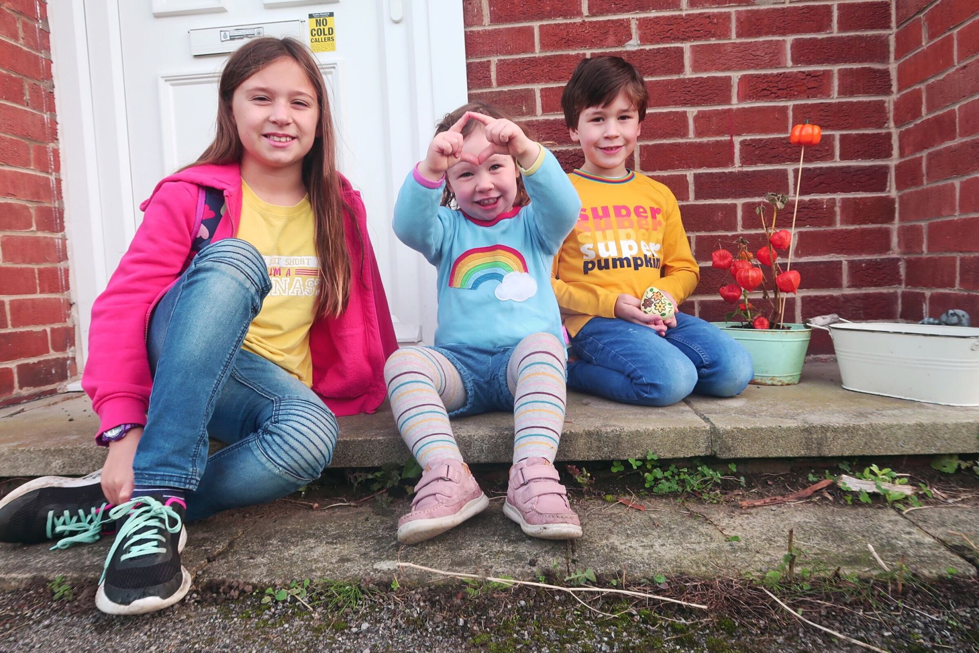 3 kids sat smiling on a step