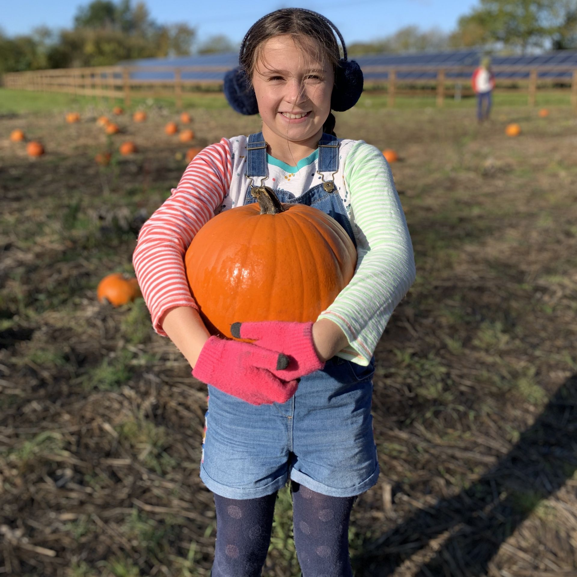 A girl holding a pumpkin smiling