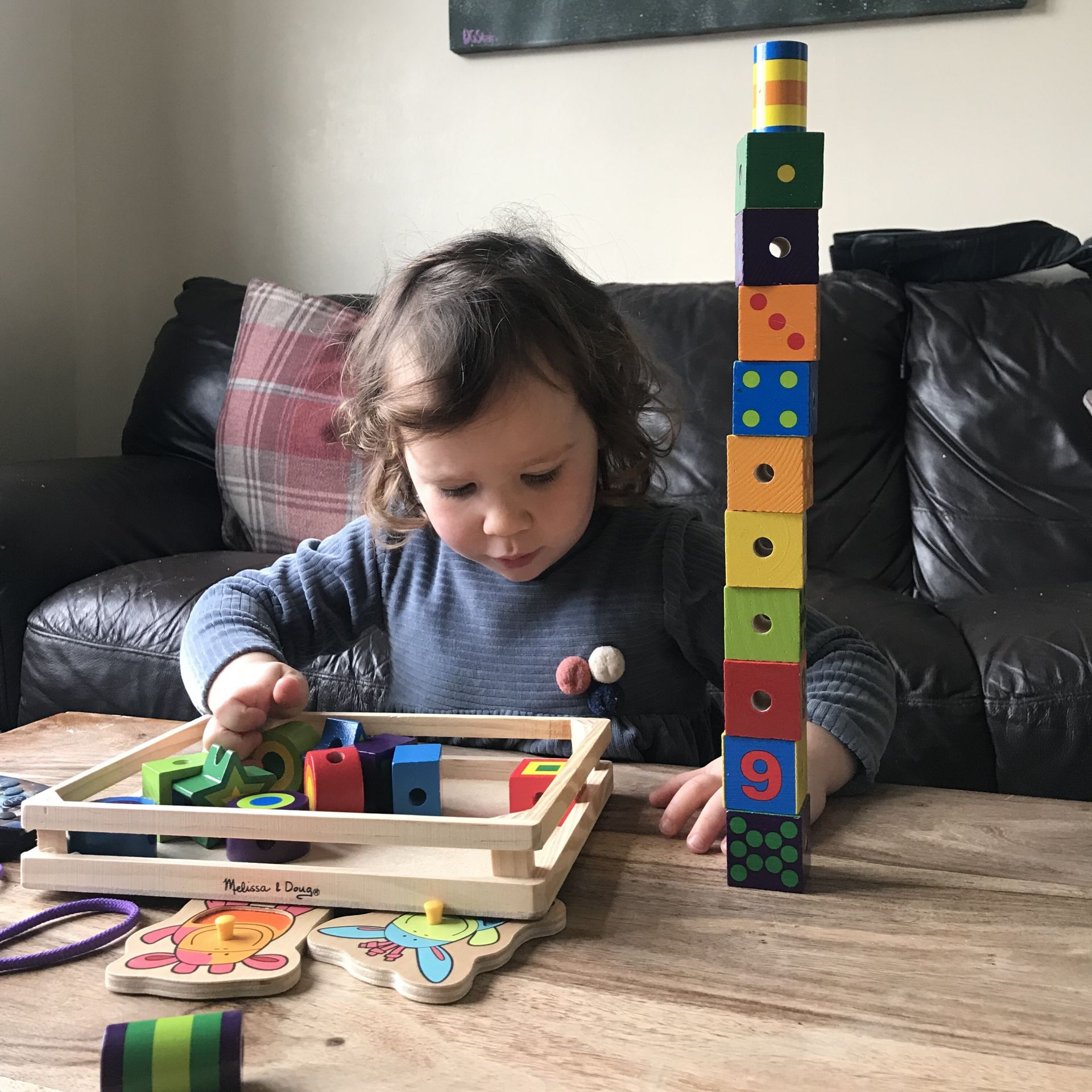 a toddler building a tower from bricks