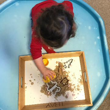 a child playing with dough for a Christmas baby and toddler activity