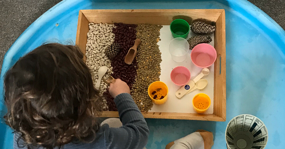 a child scooping festive coloured dried beans for a Christmas toddler activity
