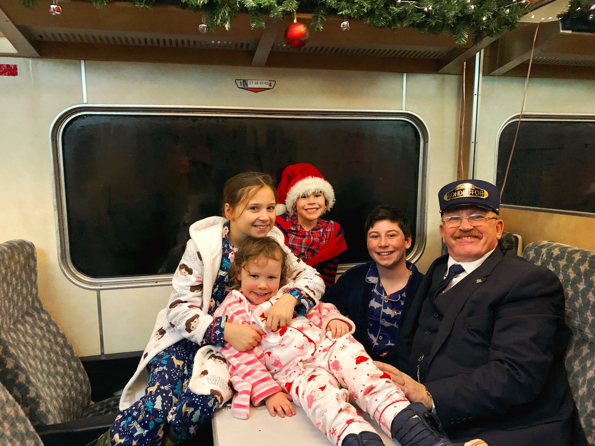 4 children posing for a picture with a train conductor