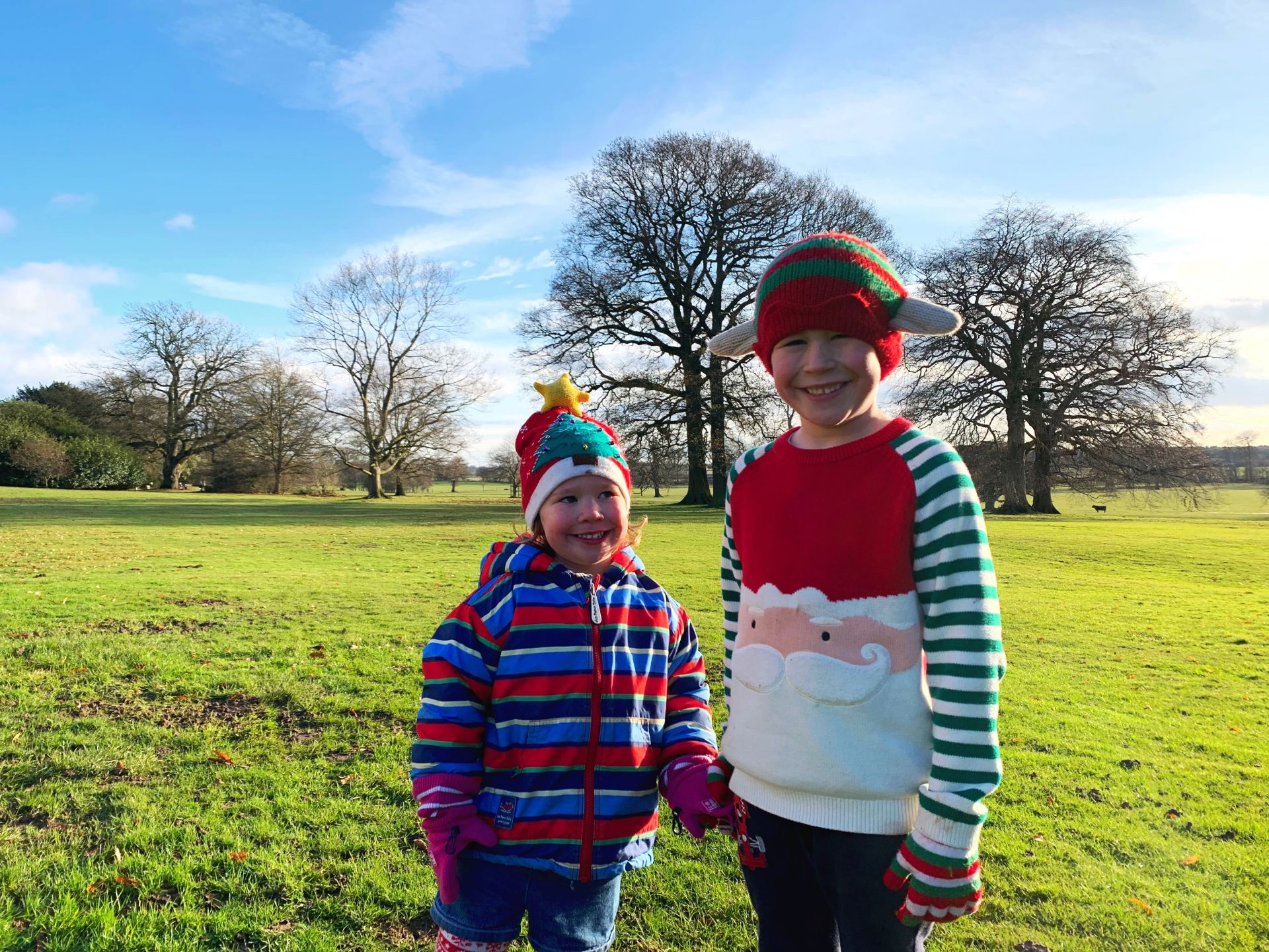 two young children wearing Christmas clothing