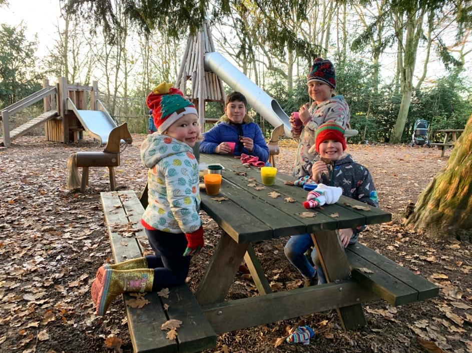 four children having a picnic in the woods in winter