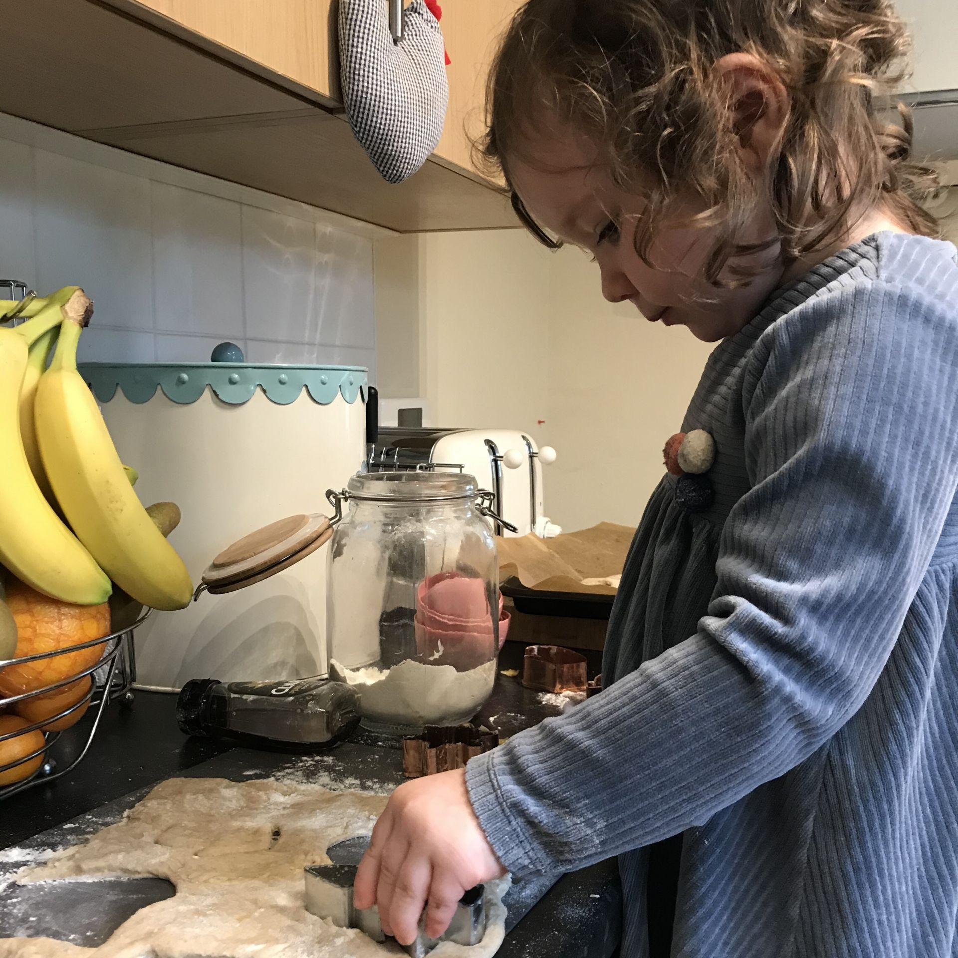 a small girl baking in the kitchen