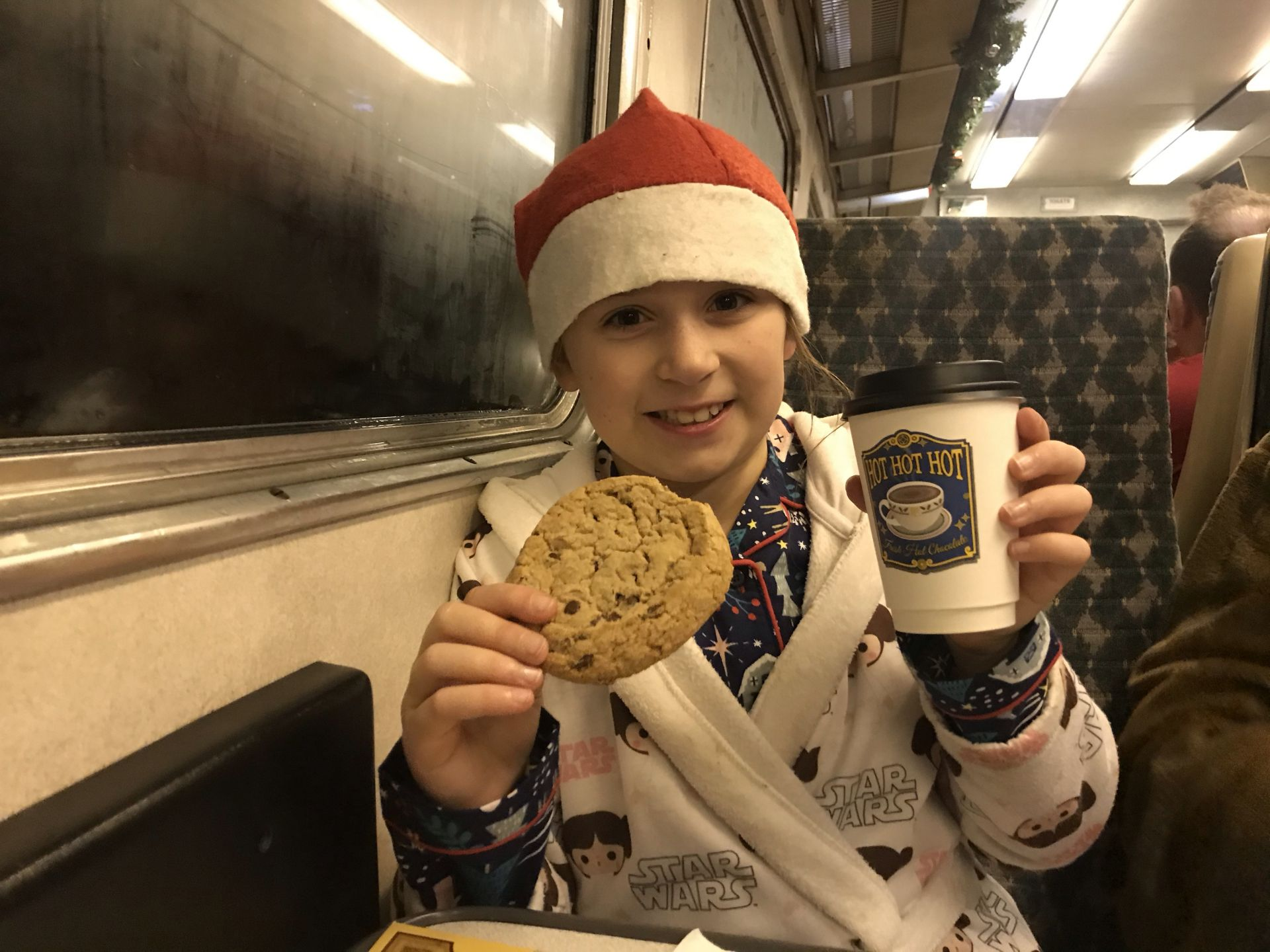 a girl having hot chocolate and a cookie