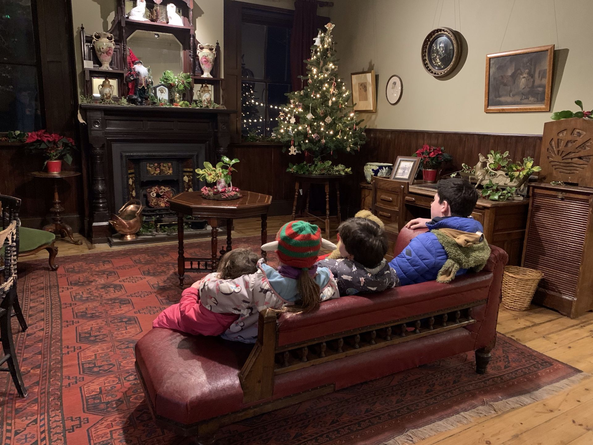 children sat on a sofa I a christmassy room