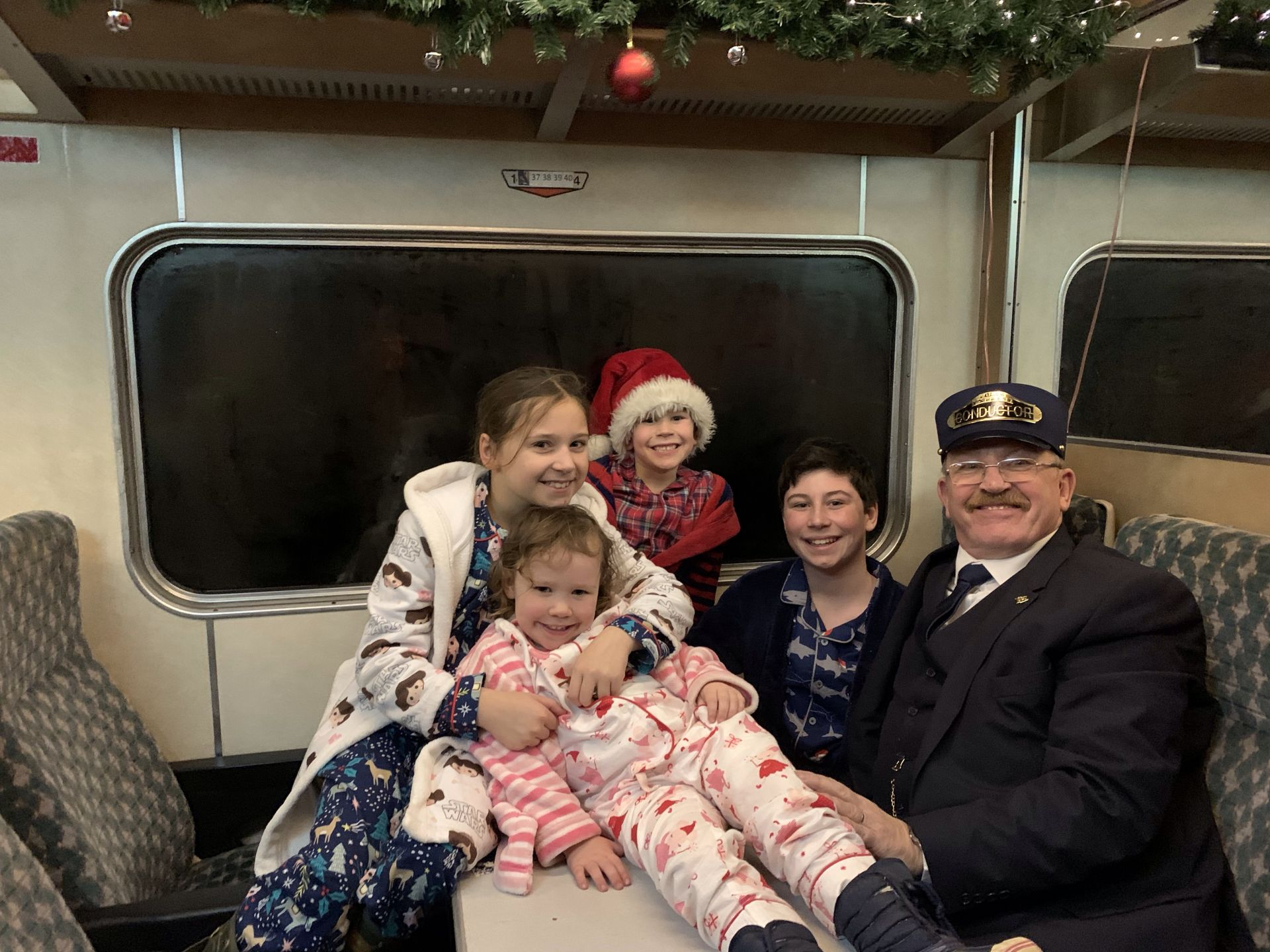 four children posing for a picture with a train conductor