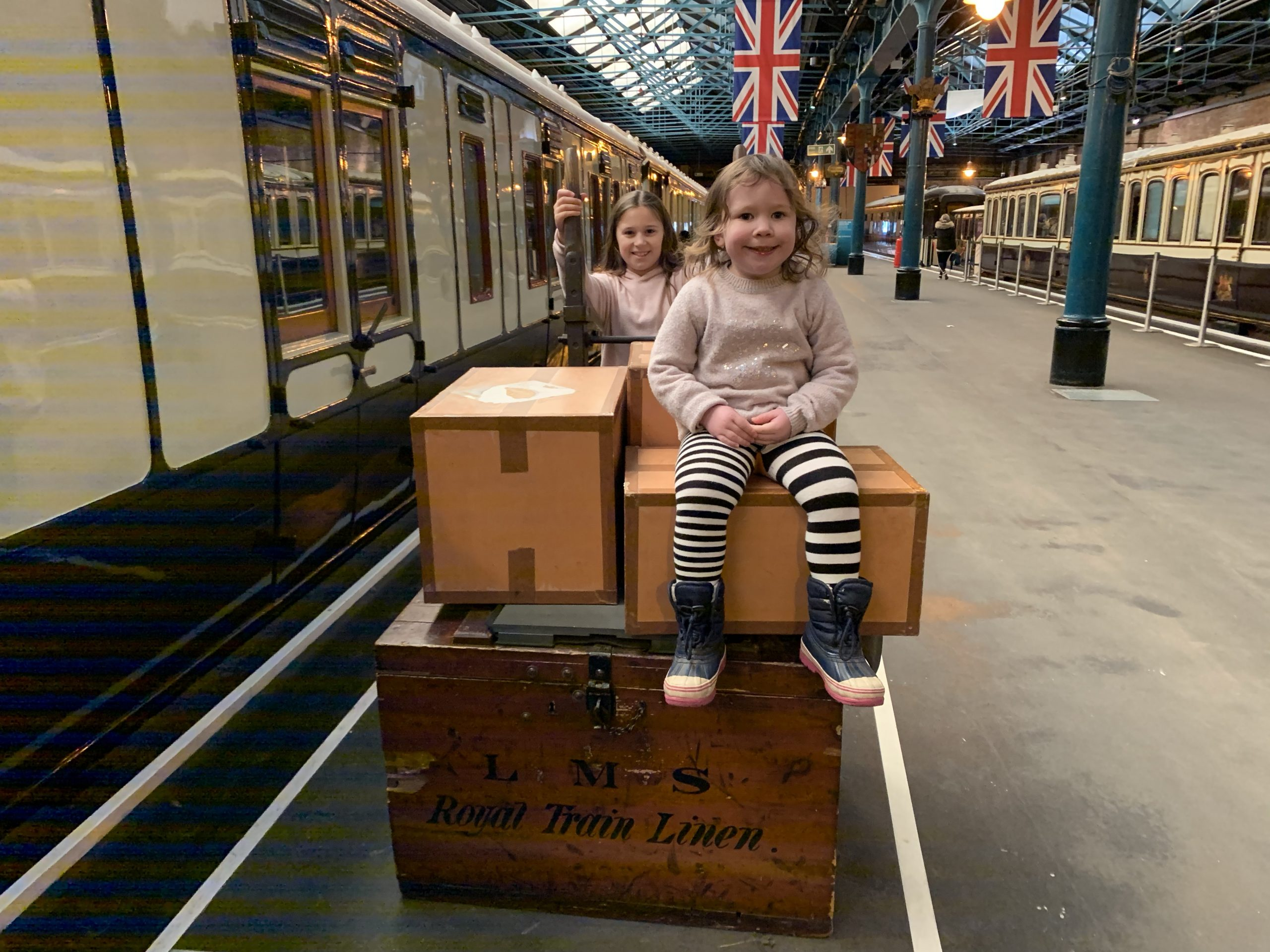 two girls sat on a luggage wagon in the railway museum