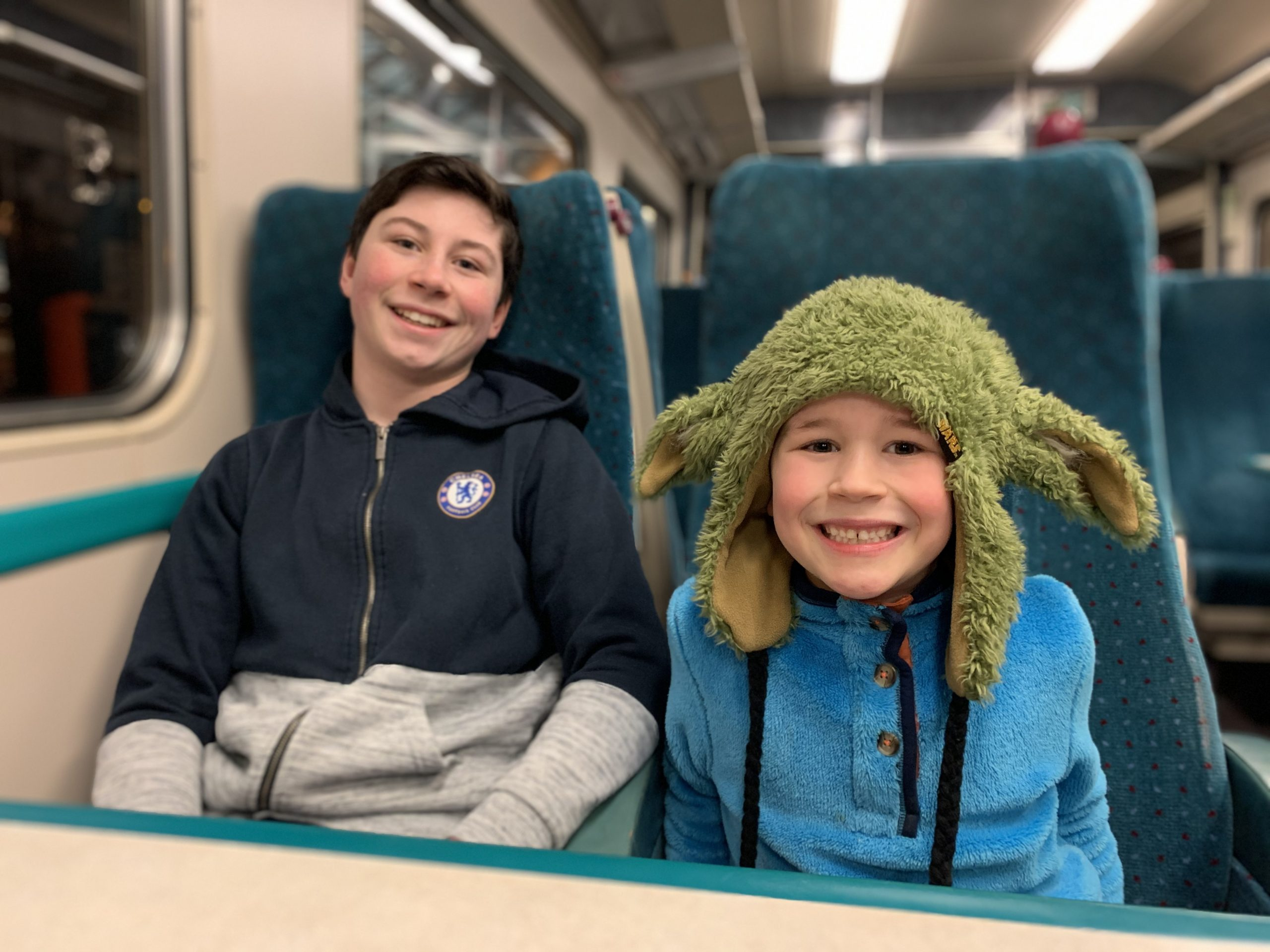 two boys sat in a train carriage posing for a photo