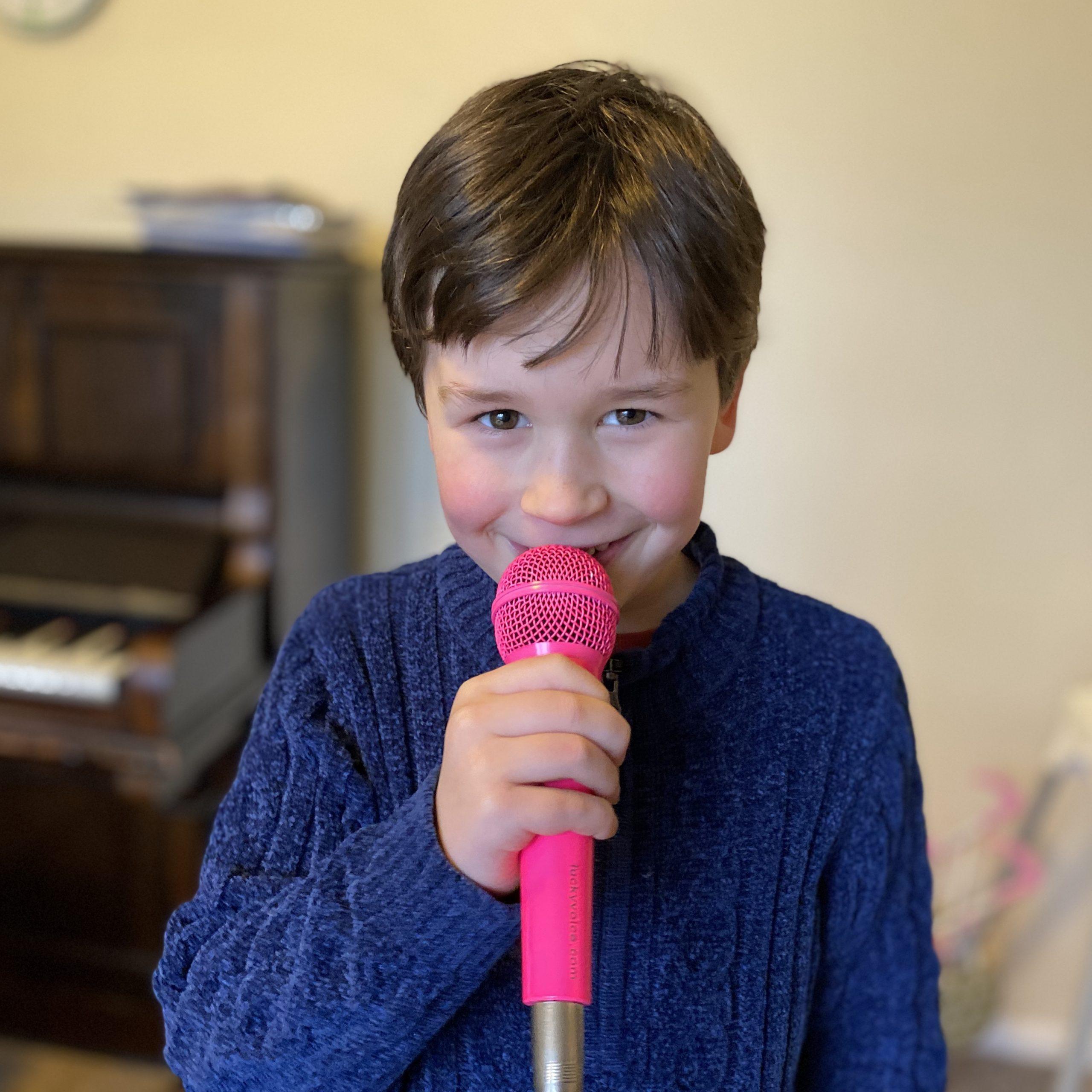 a boy singing in a microphone