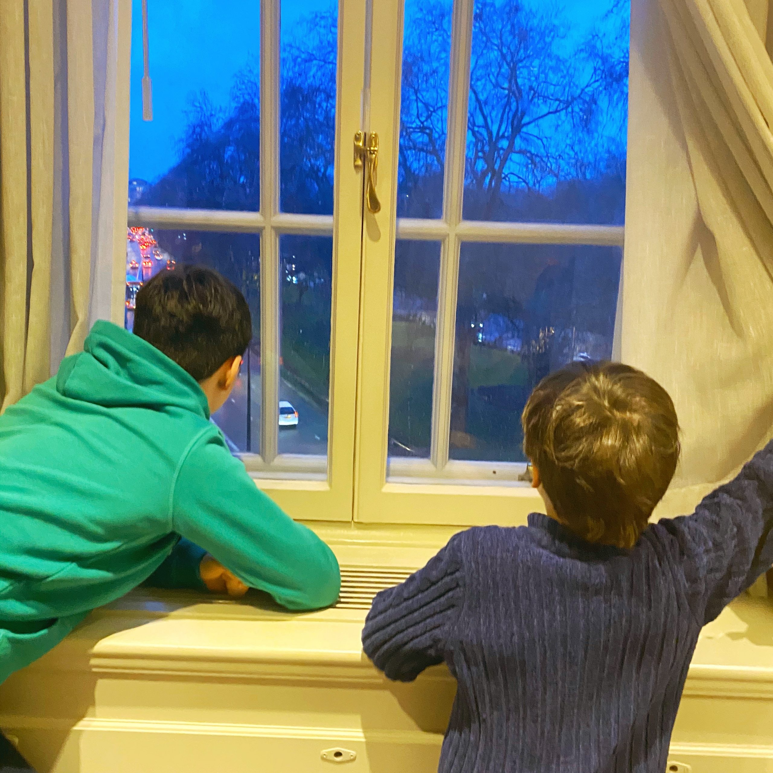 Family life with two boys looking out of a window at cars