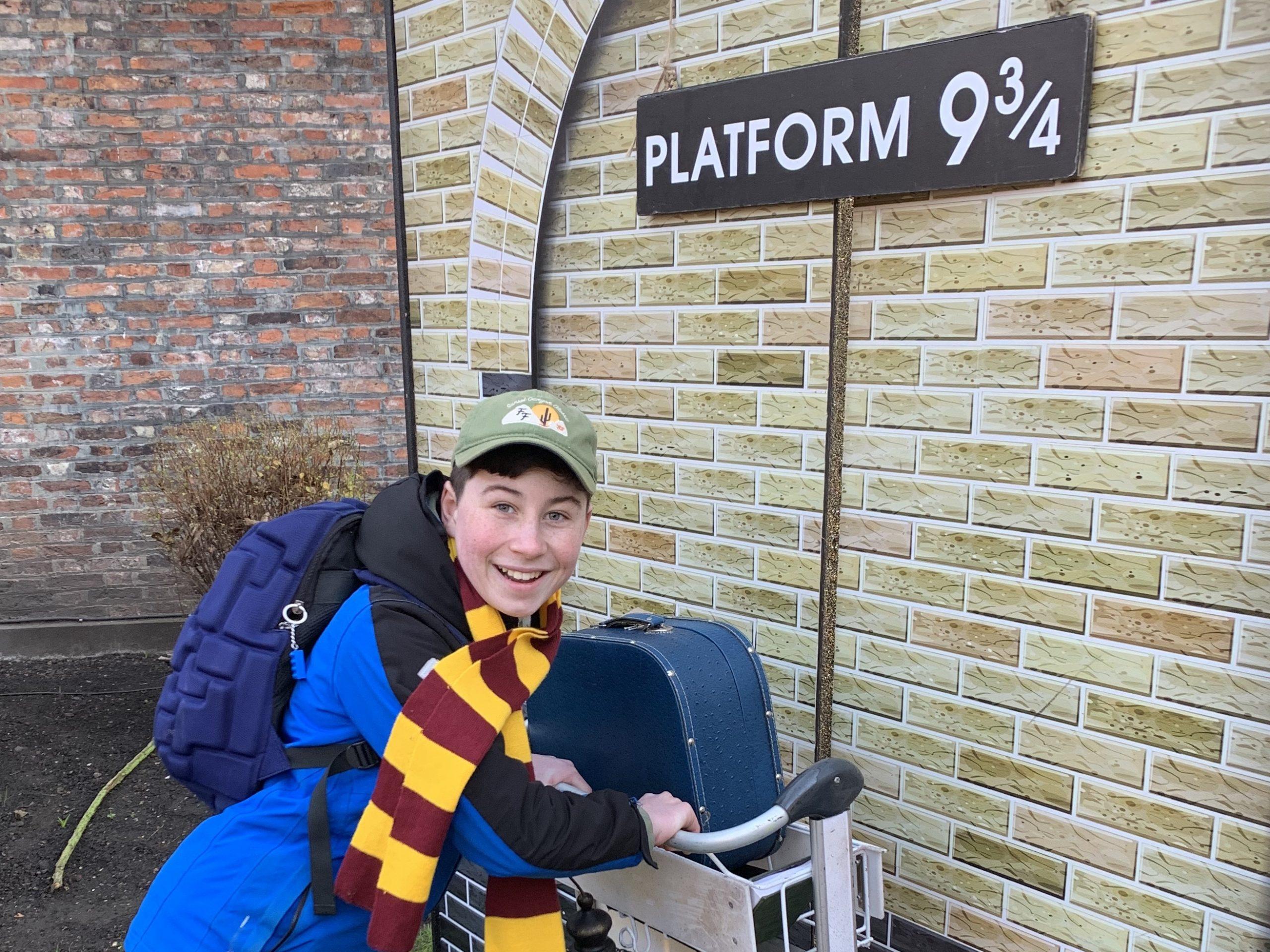 a boy running towards Hogwarts platform 9 3/4 with a trolley