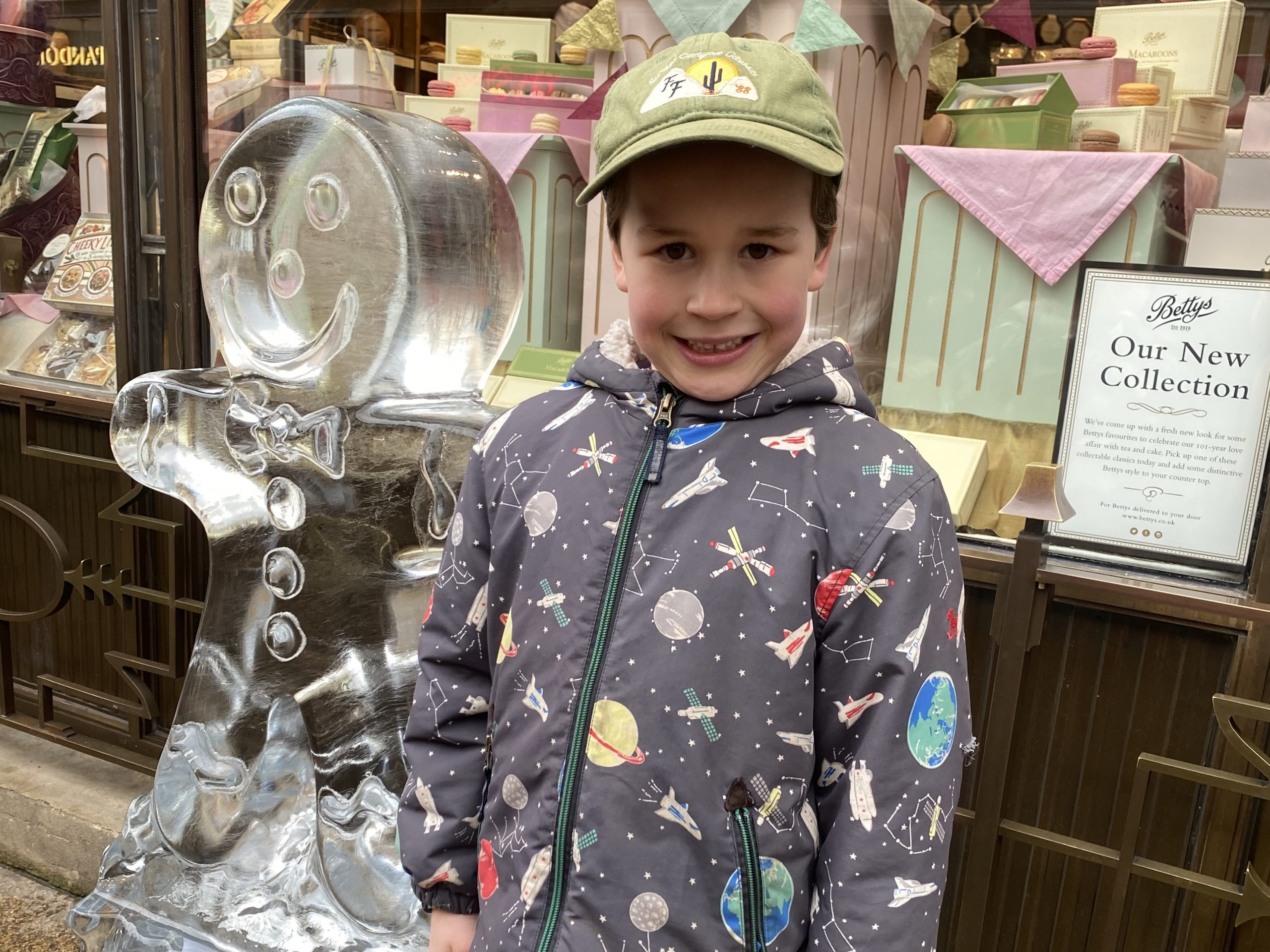 Family life outing with a boy stood next to a gingerbread man ice sculpture.
