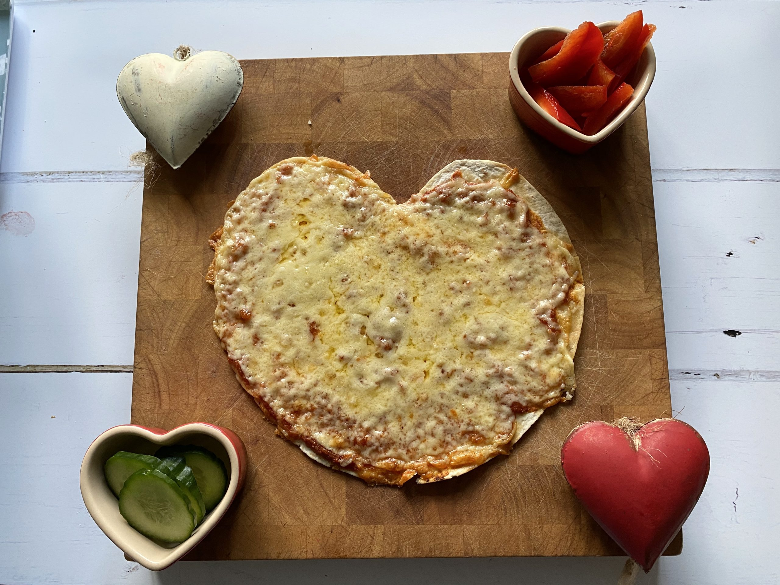 homemade tortilla pizza with hearts around it and cucumber and pepper