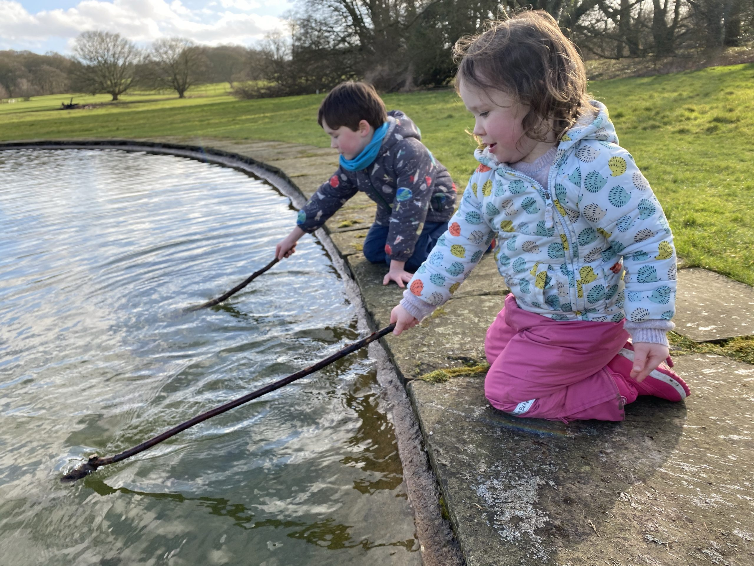 Two small children playing by a pond with sticks