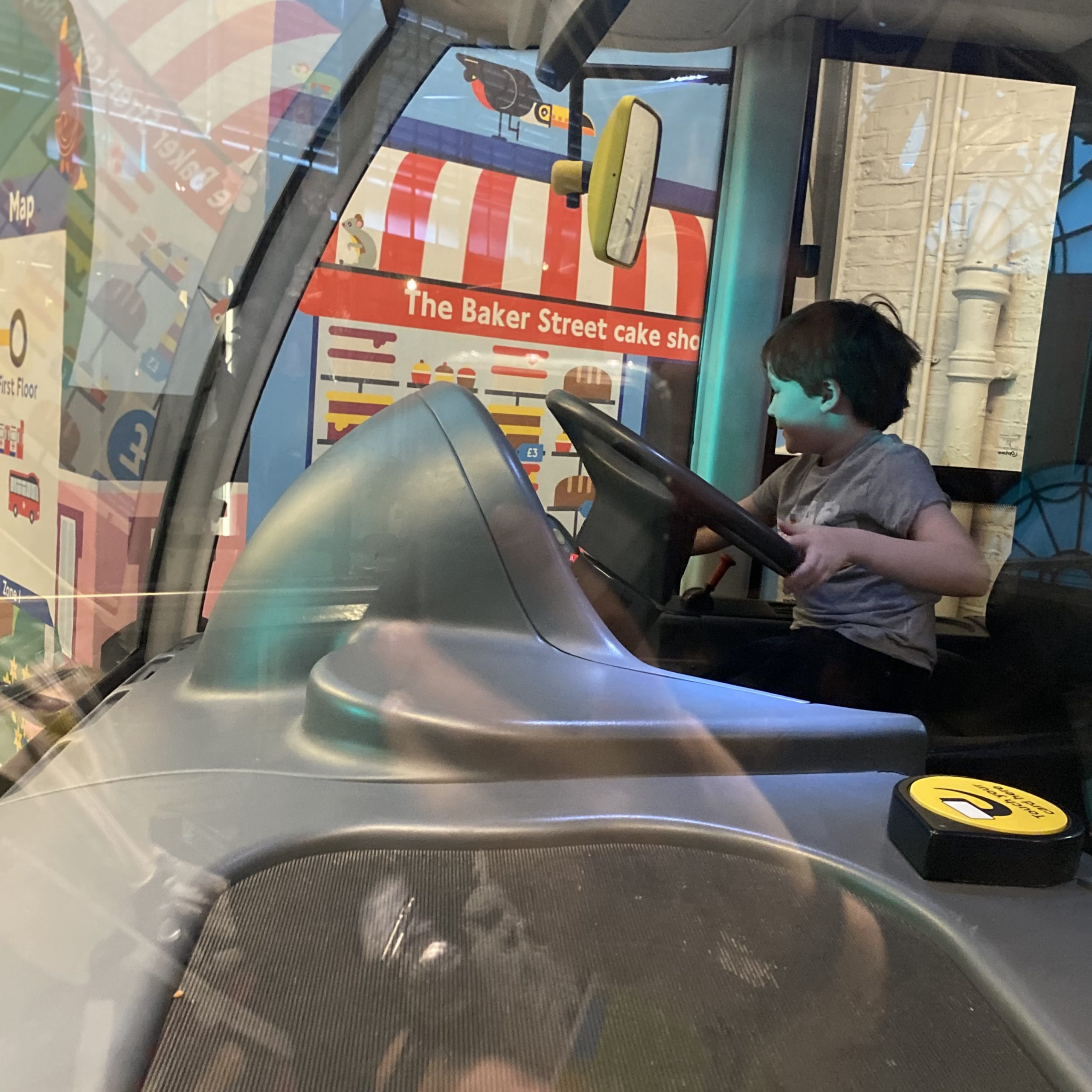 A boy driving a play bus at the LT museum