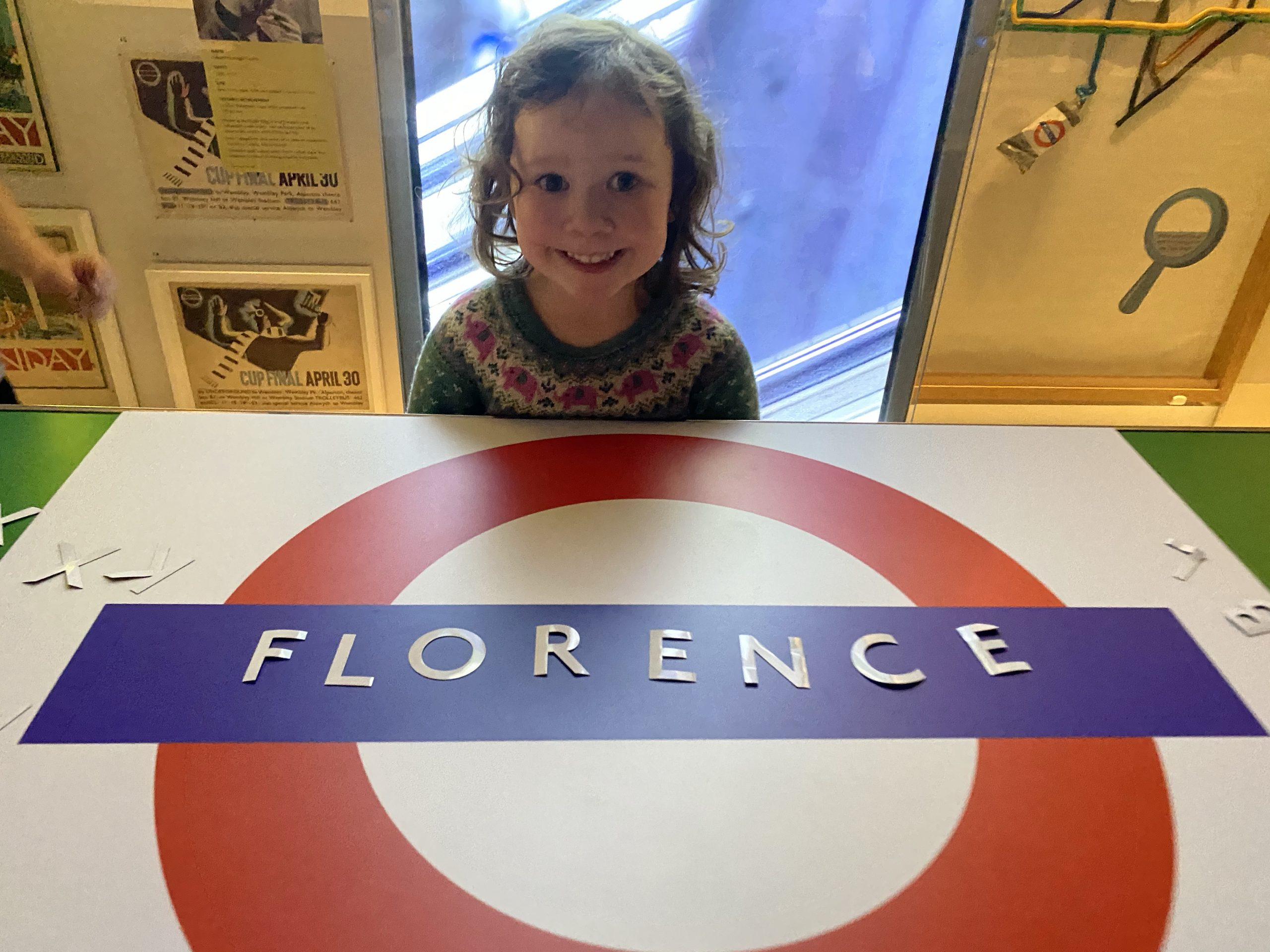 A small child making her own roundel at the London Transport Museum