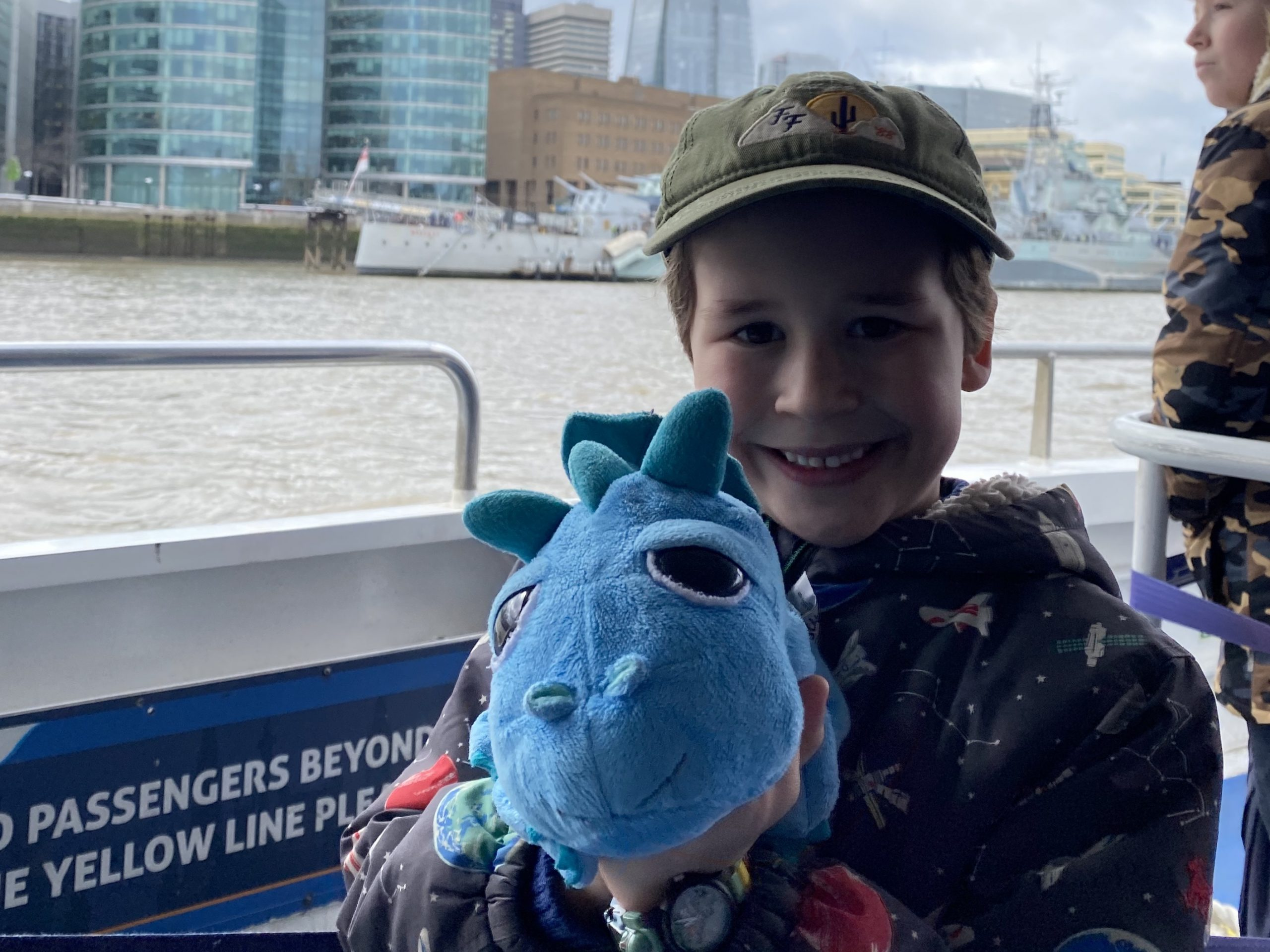 Family life in London. A boy on a boat in the Thames with a cuddly toy dragon