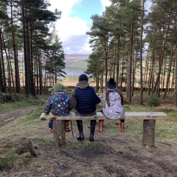 family life with 3 children sat looking at a beautiful view on a bench