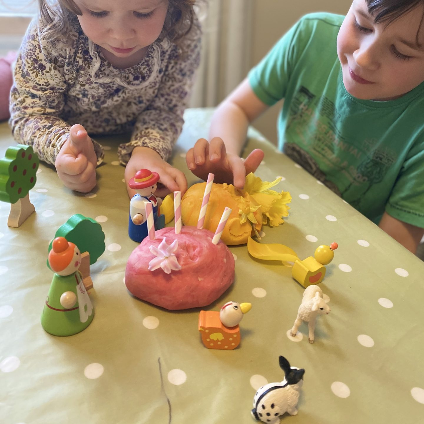 Playdough and farm animals with two children playing