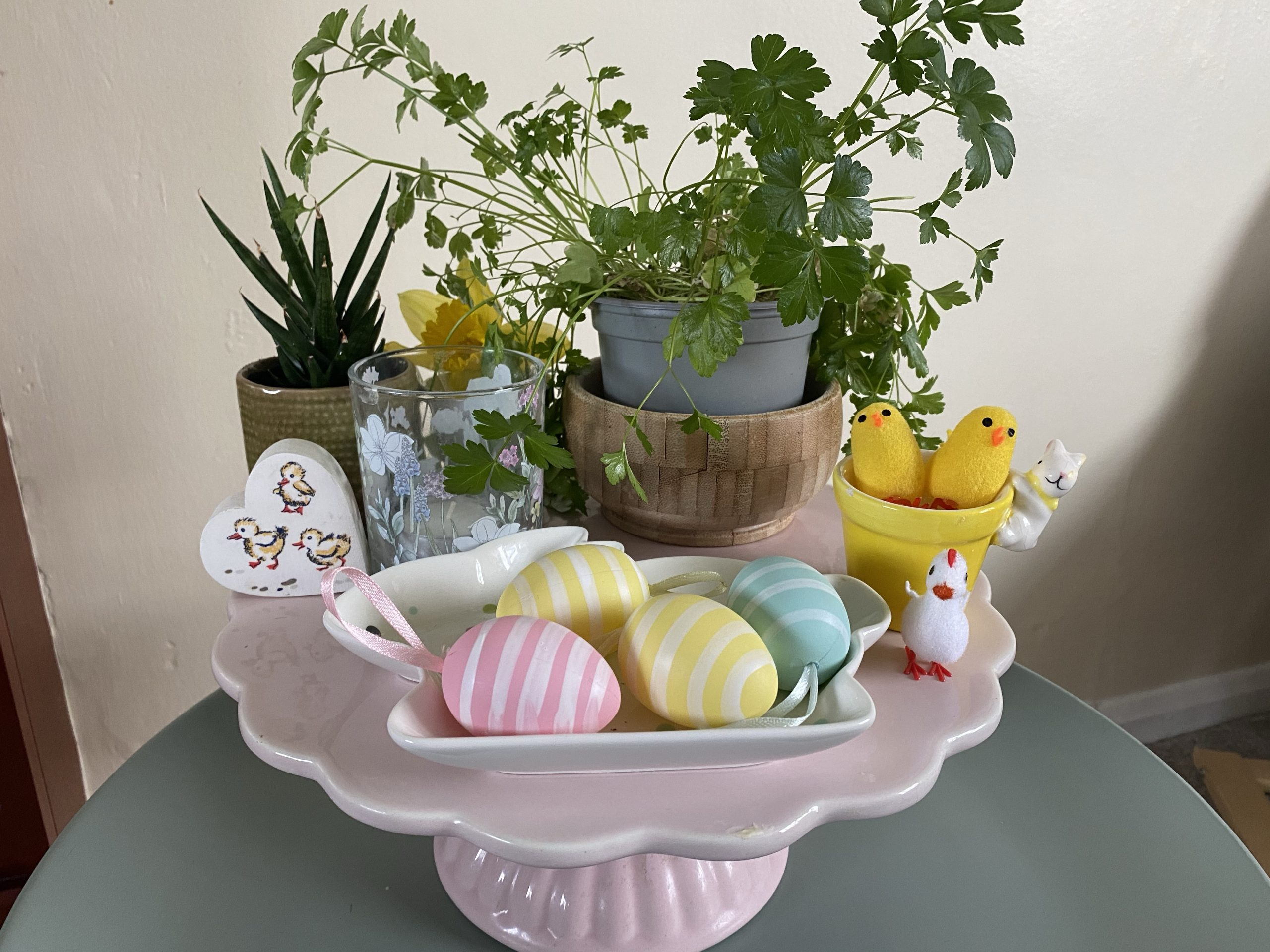 Easter Hoe decor on a budget- A cake stand filled with Easter flowers, eggs and chicks