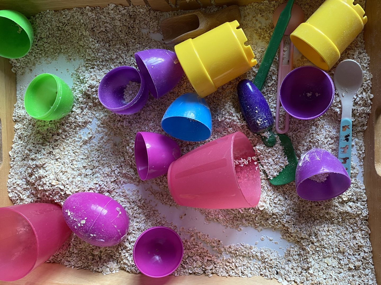 Spring sensory play  - a tray with oats and plastic eggs