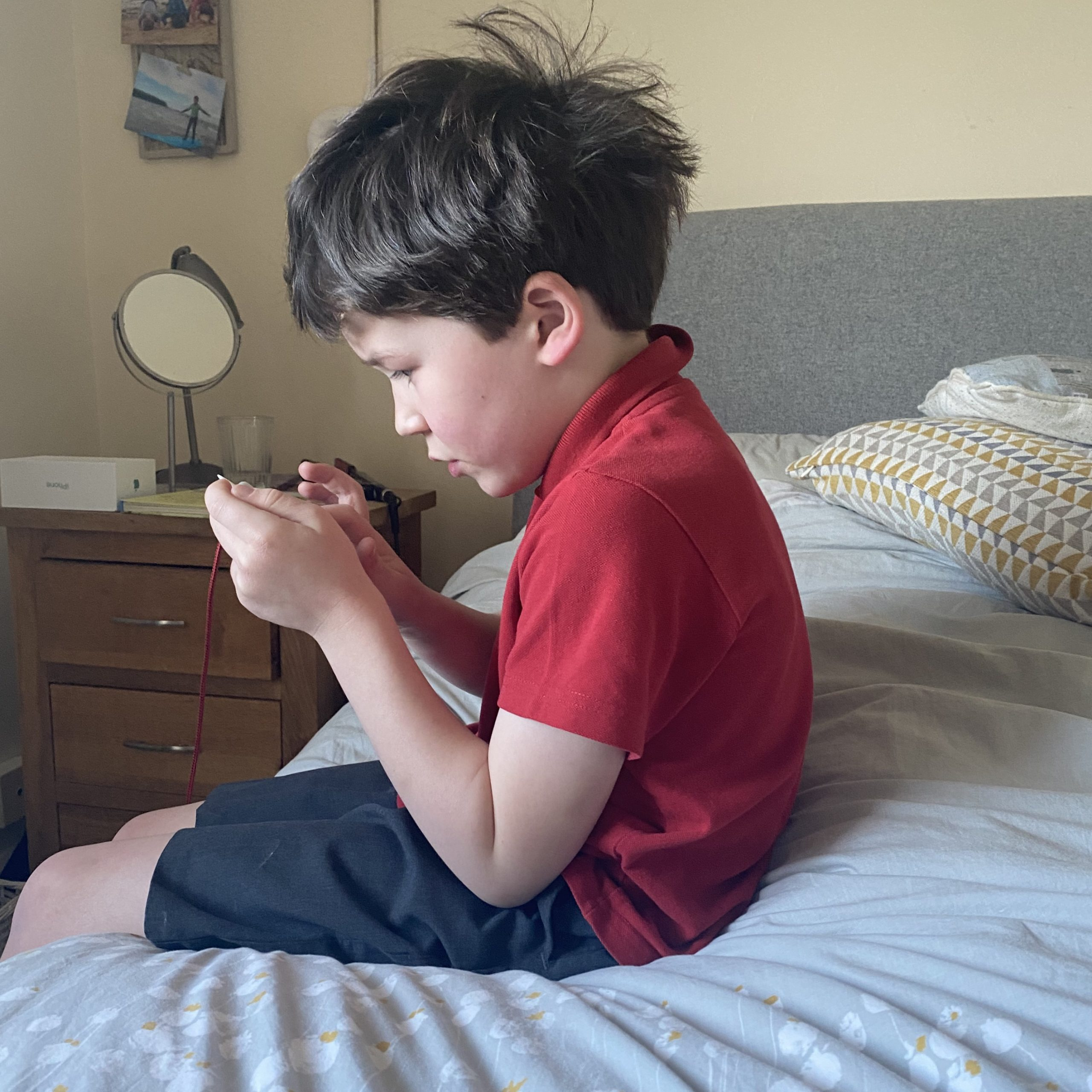 Family Life with a boy sat playing an online game on a bed