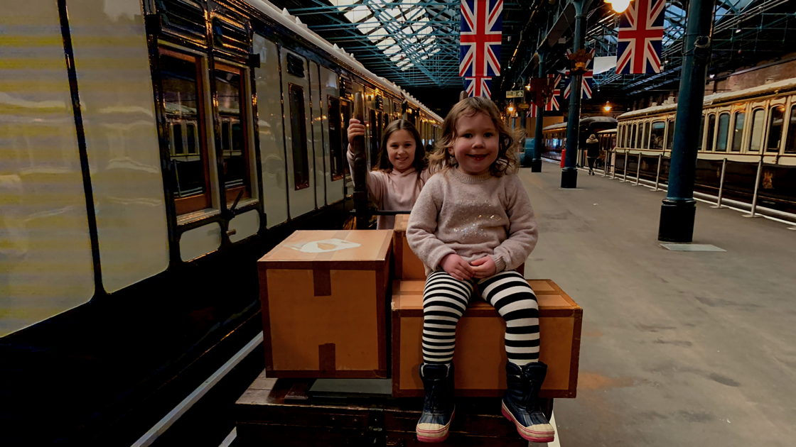 2 children on a luggage cart by a train