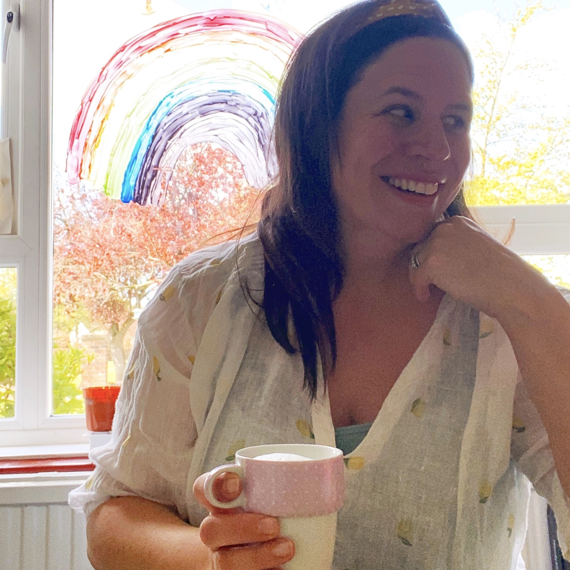 a woman drinking coffee and smiling by her stay safe indoors rainbow on her window