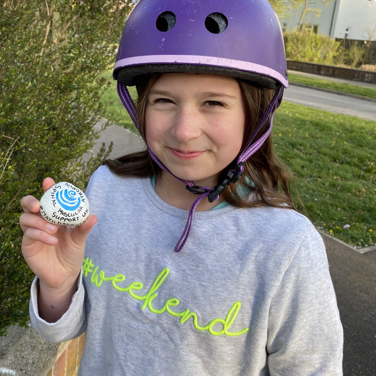 a girl holding a painted rock with a nice smile on her face