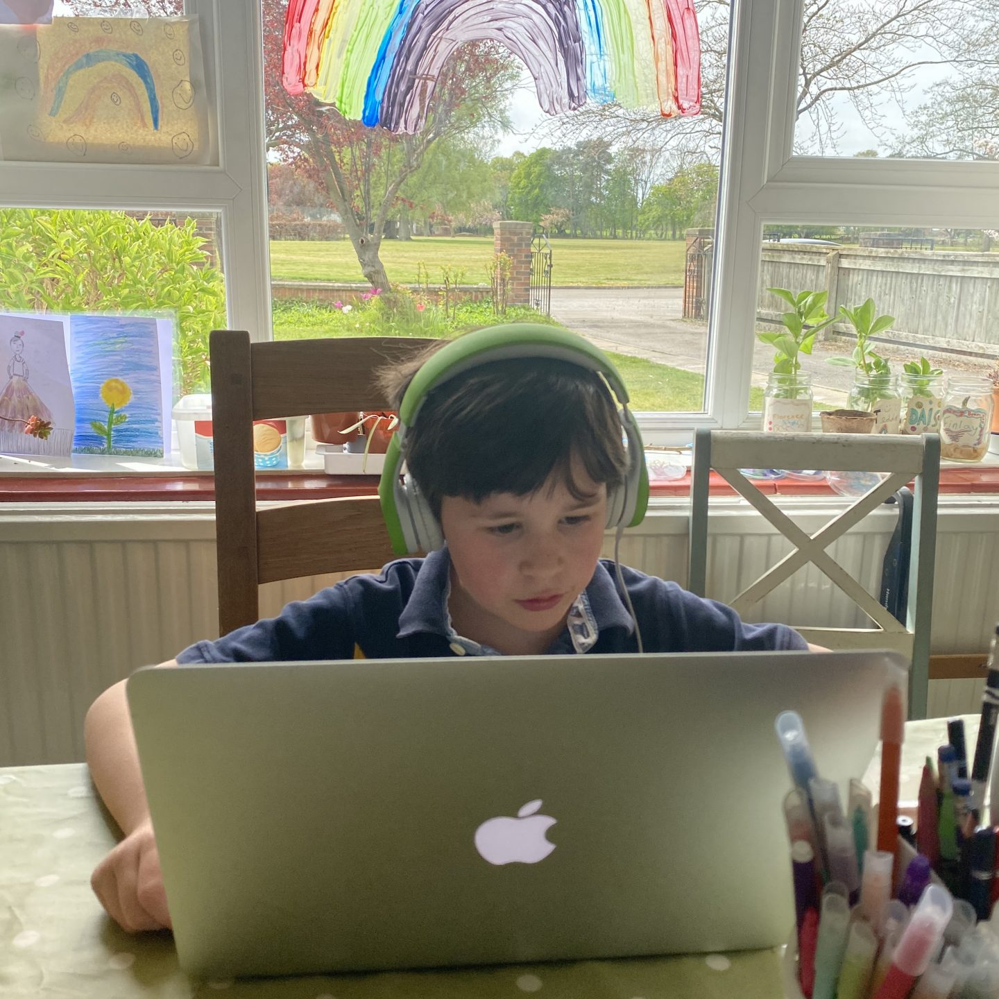 Living arrows with a boy studying with  a MacBook and headphones on