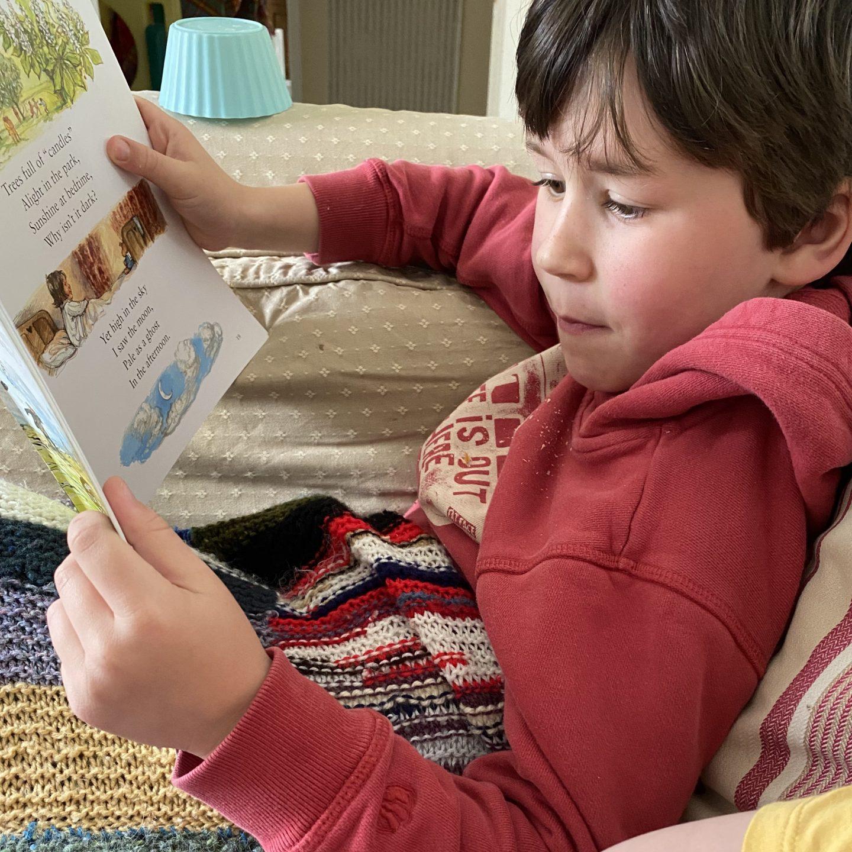 a boy snuggled under a blanket reading