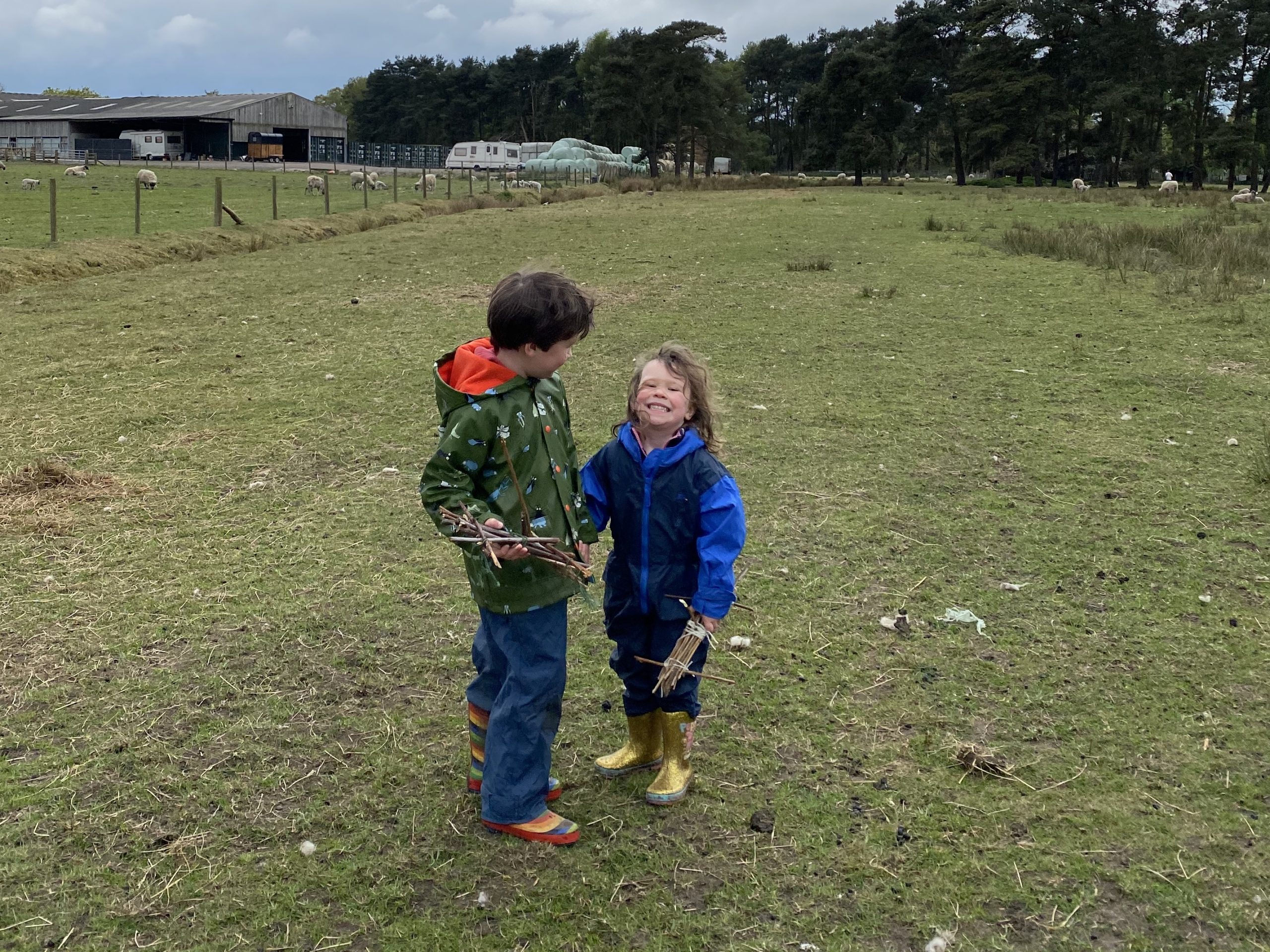 two children in a field grinning at the camera with sticks in their hands