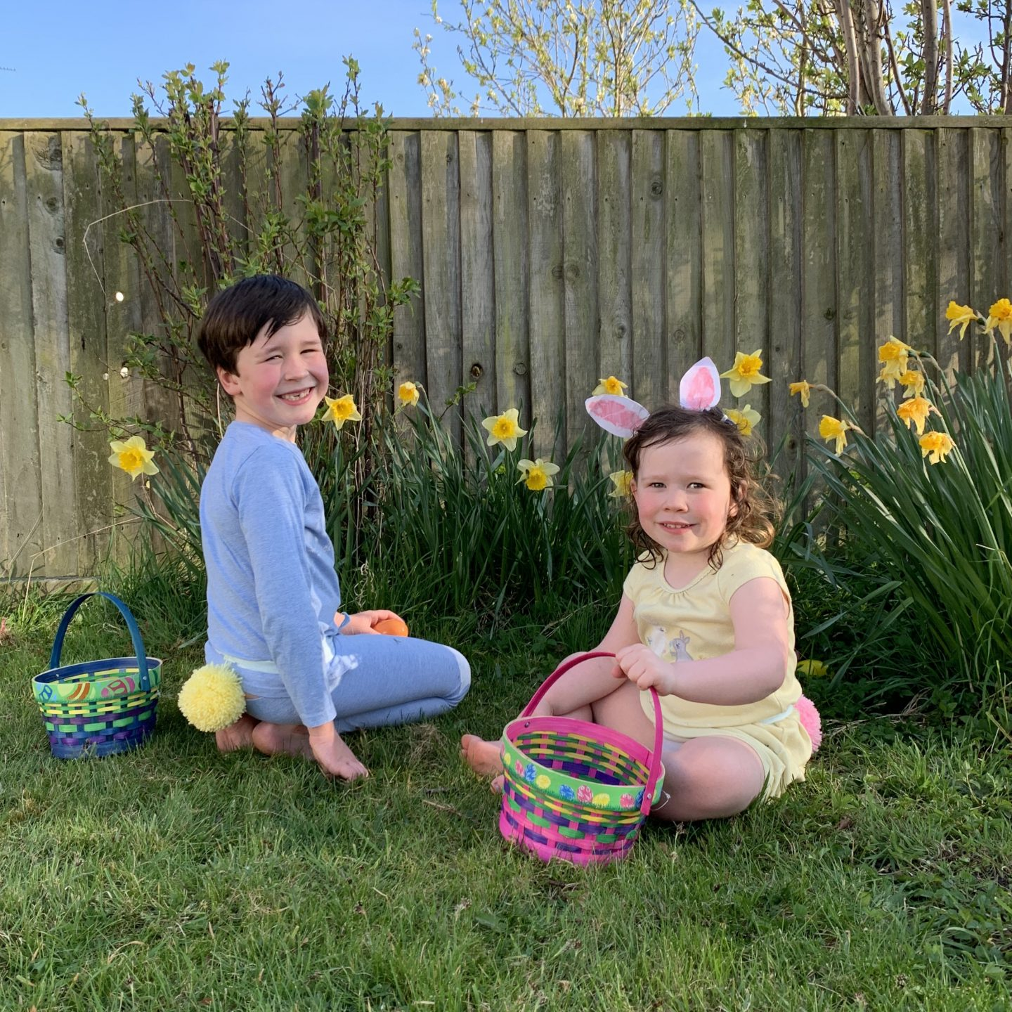 Two children collecting eggs with bunny tails and baskets