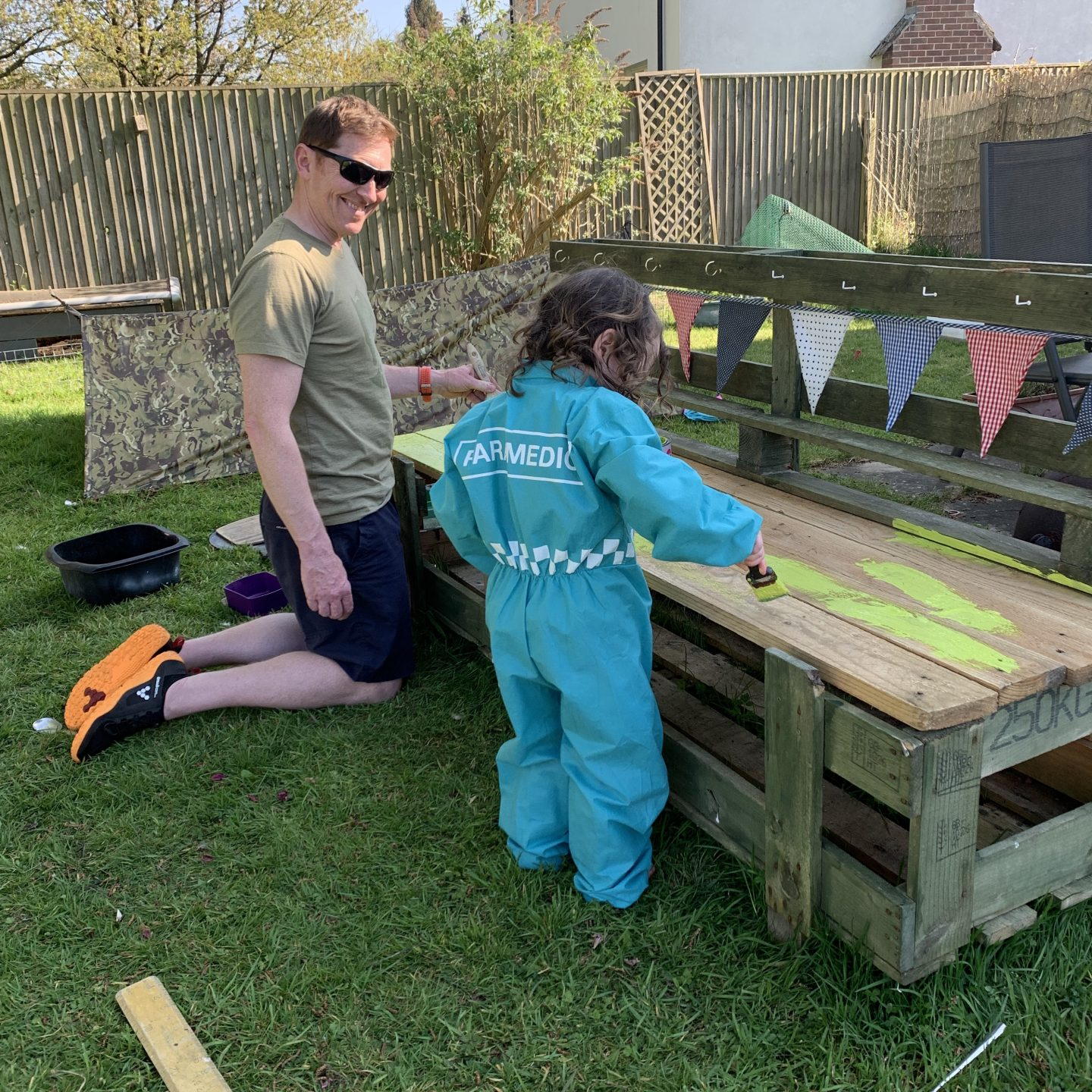 Father and daughter painting a mud kitchen