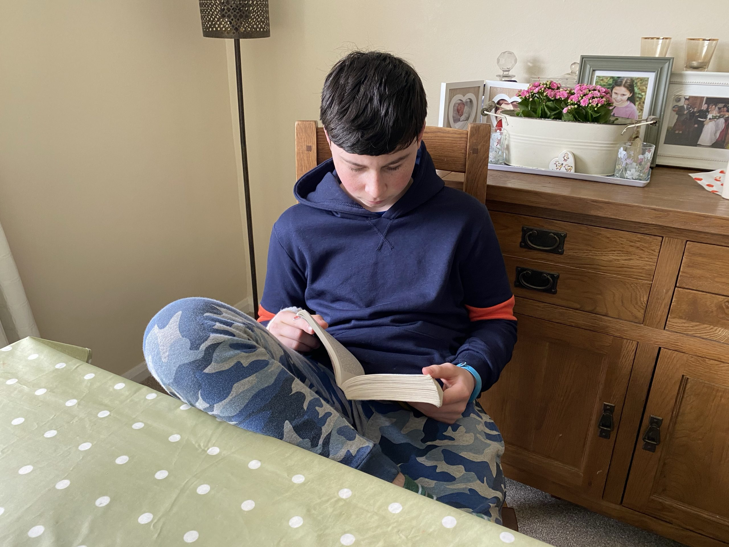 a young boy reading a book during downtime of home school