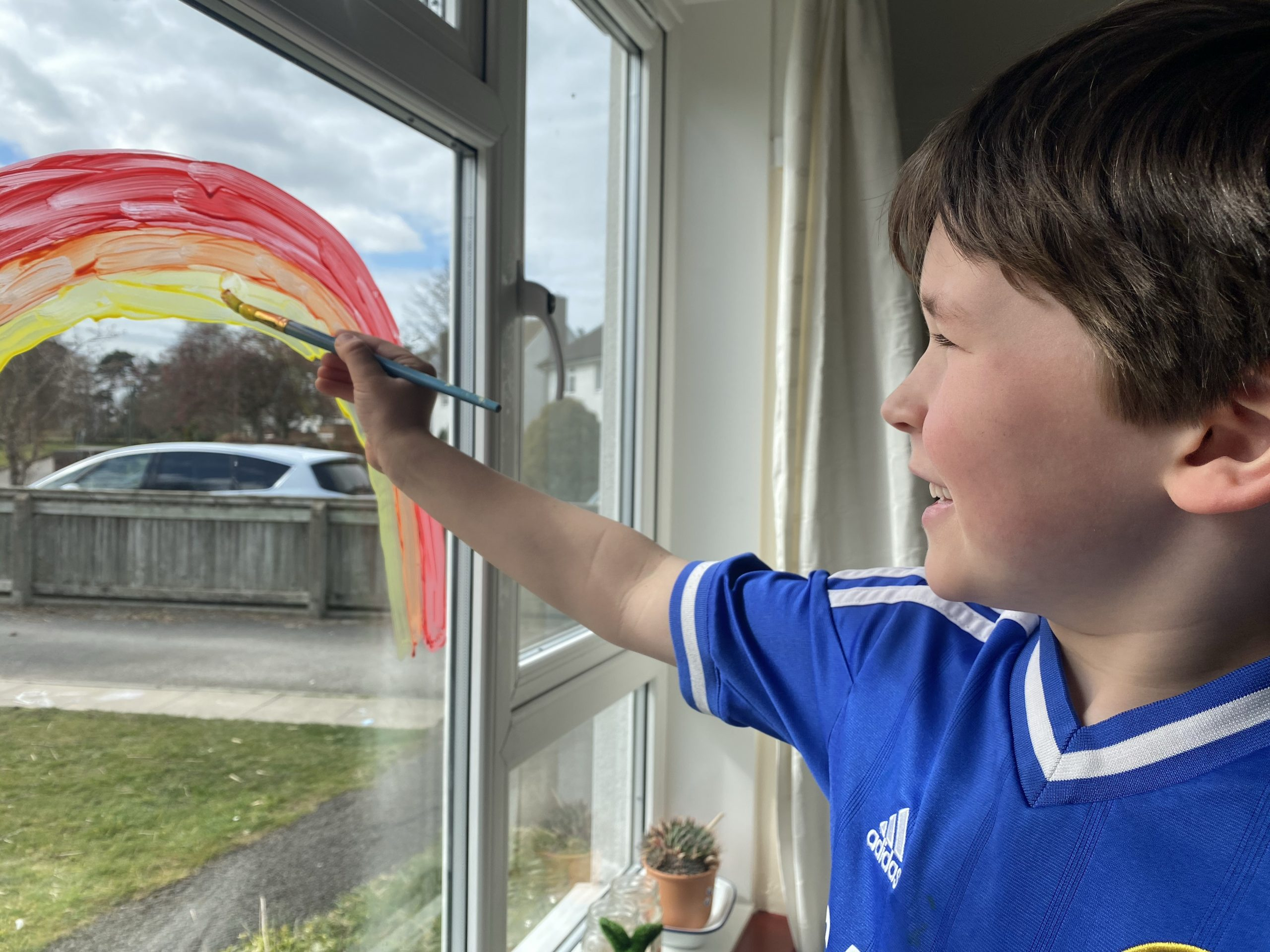 A young boy painting a rainbow on a window
