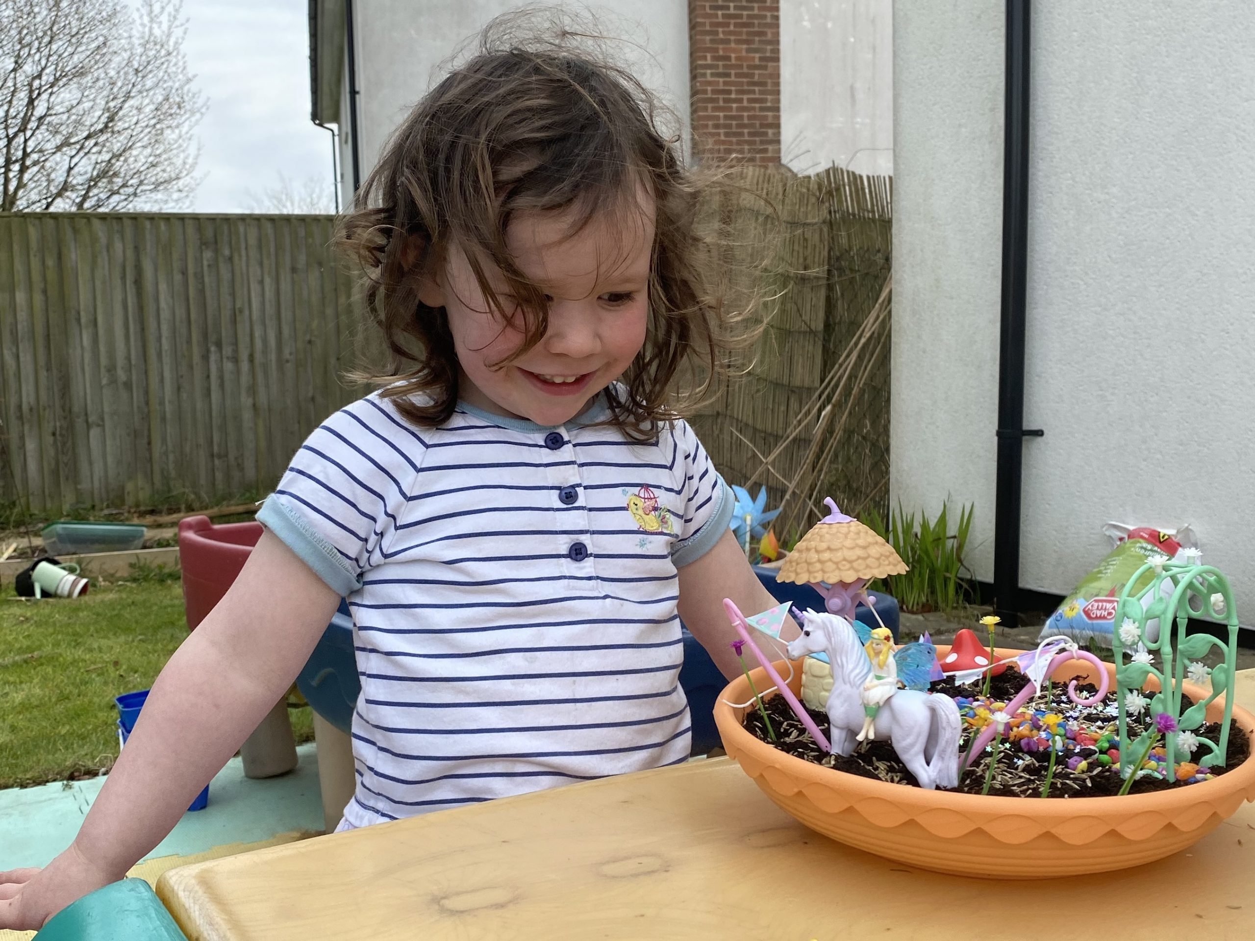 A young girl making a fairy garden