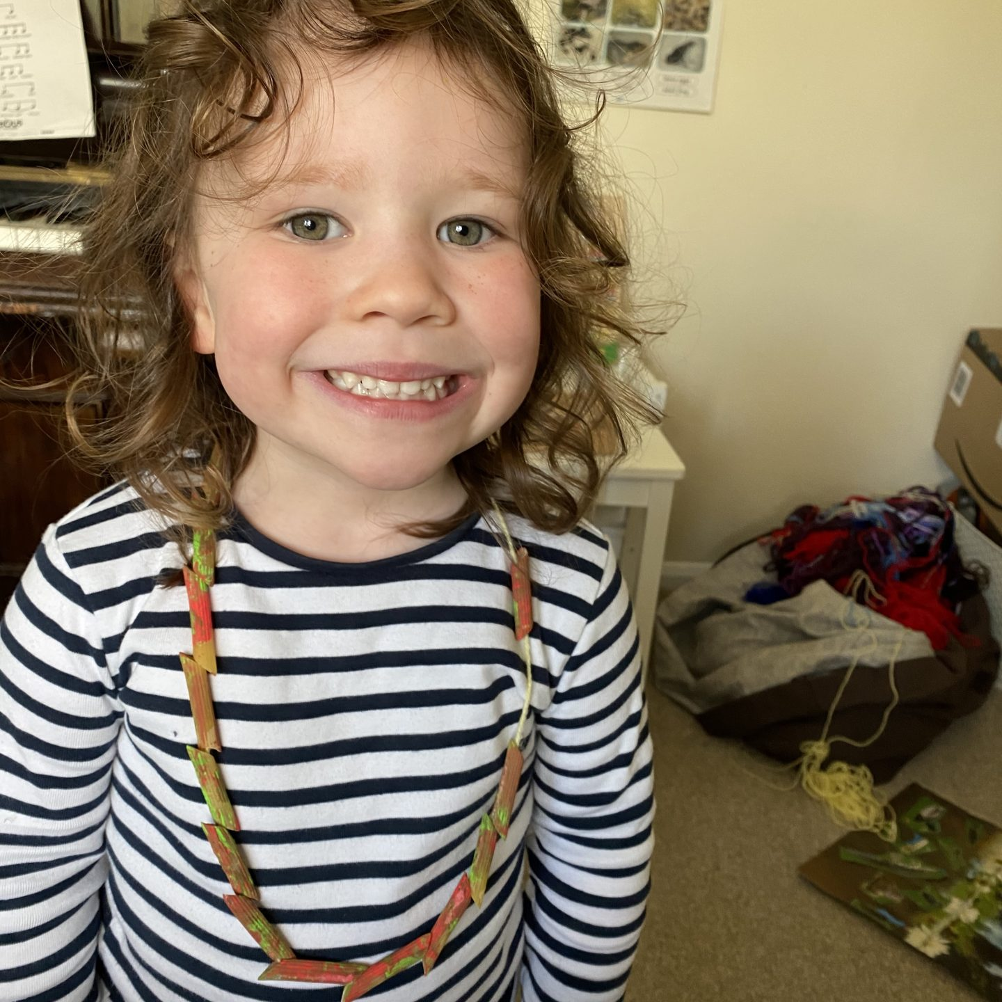 A girl showing off her homeschool creations of a pasta necklace