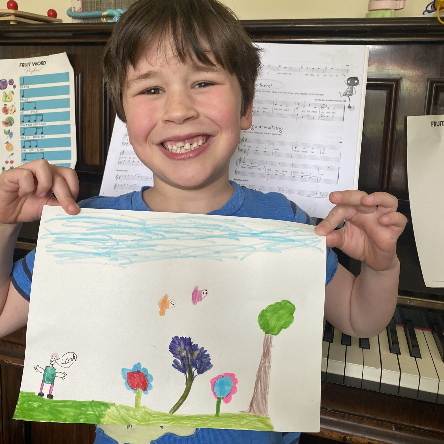Home school creations   - a boy holding a flower picture and smiling proudly