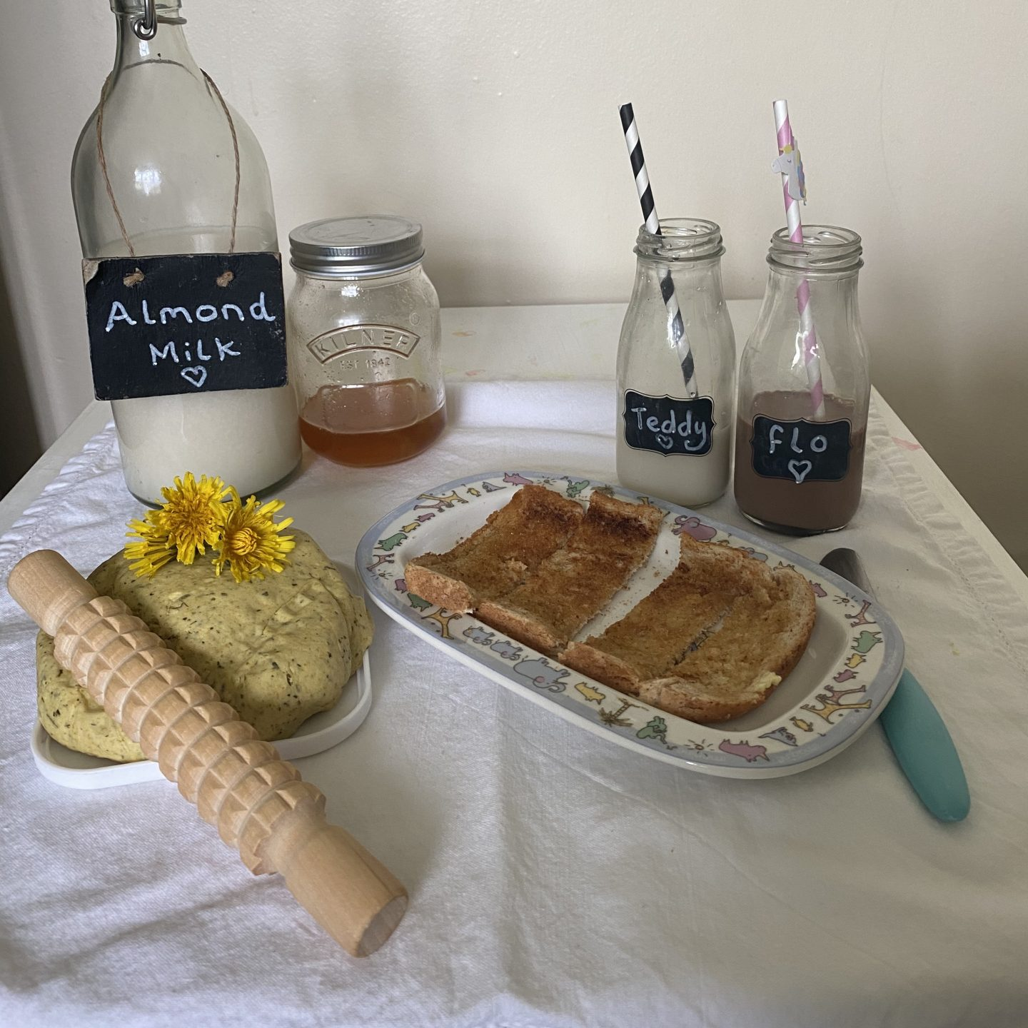 A table of self care with almond milk, toast, honey and playdough.