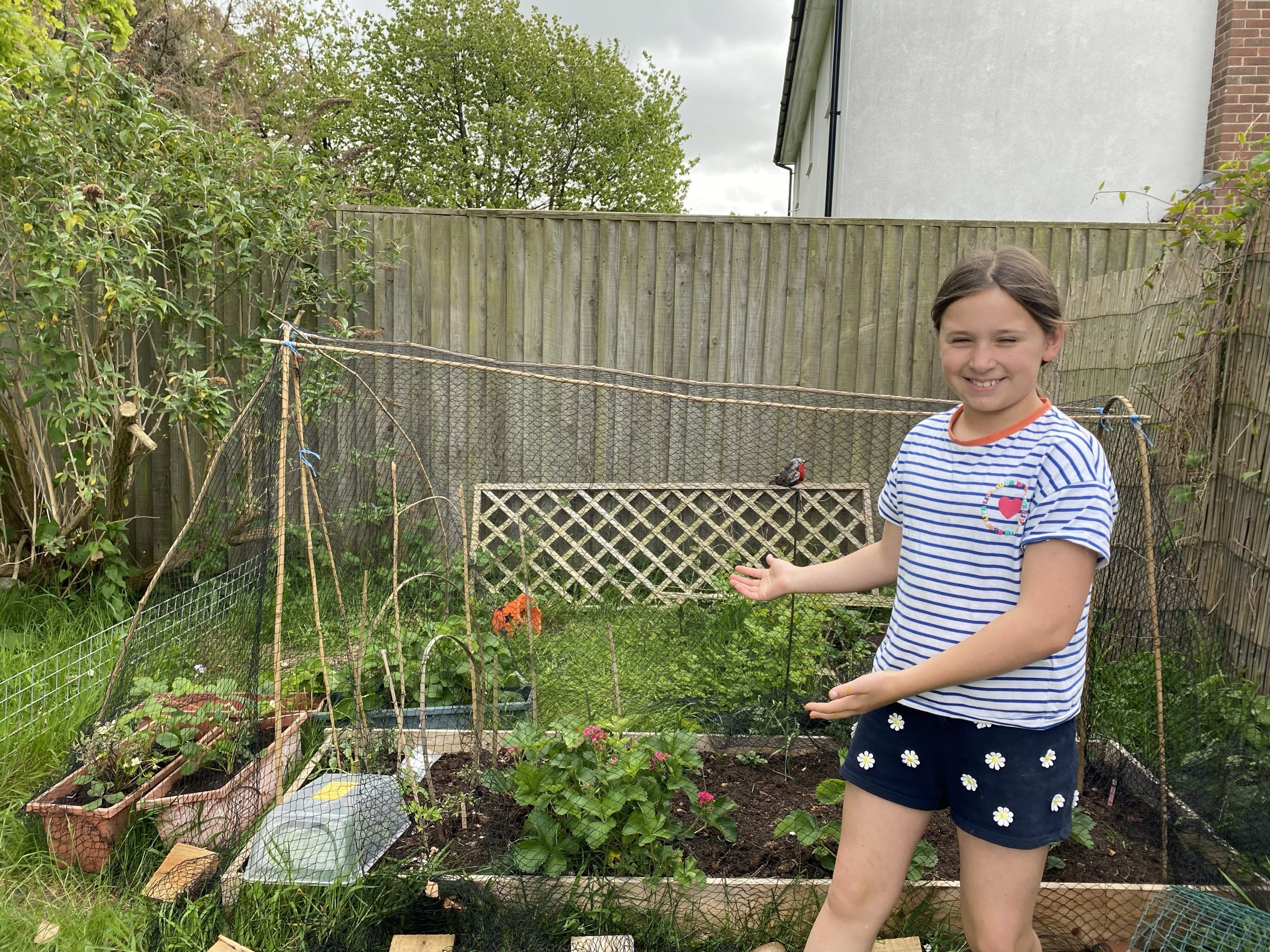 garden projects with a young girl posing by a veg patch